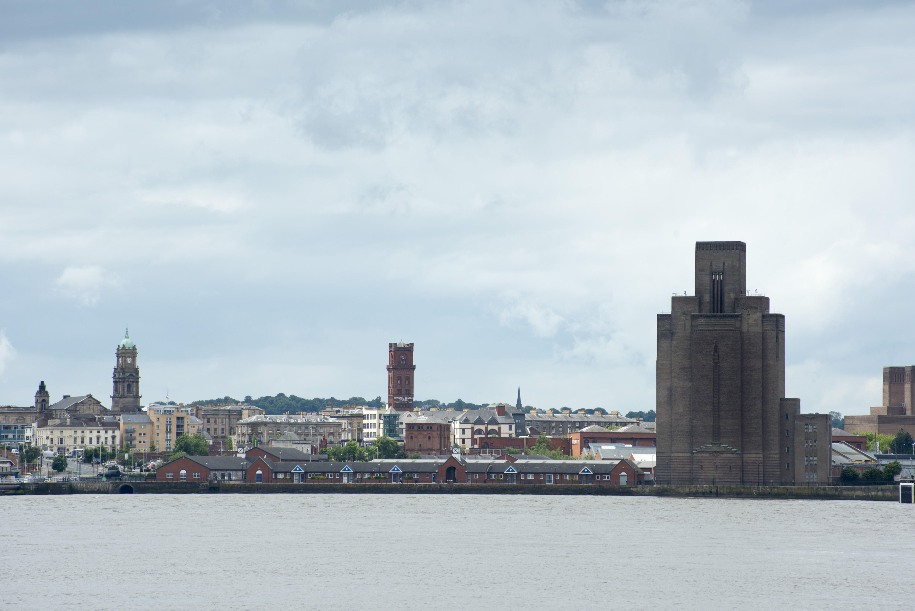 Skyline view of the Birkenhead Mersey Waterfront buildings under cloudy skies with copy space