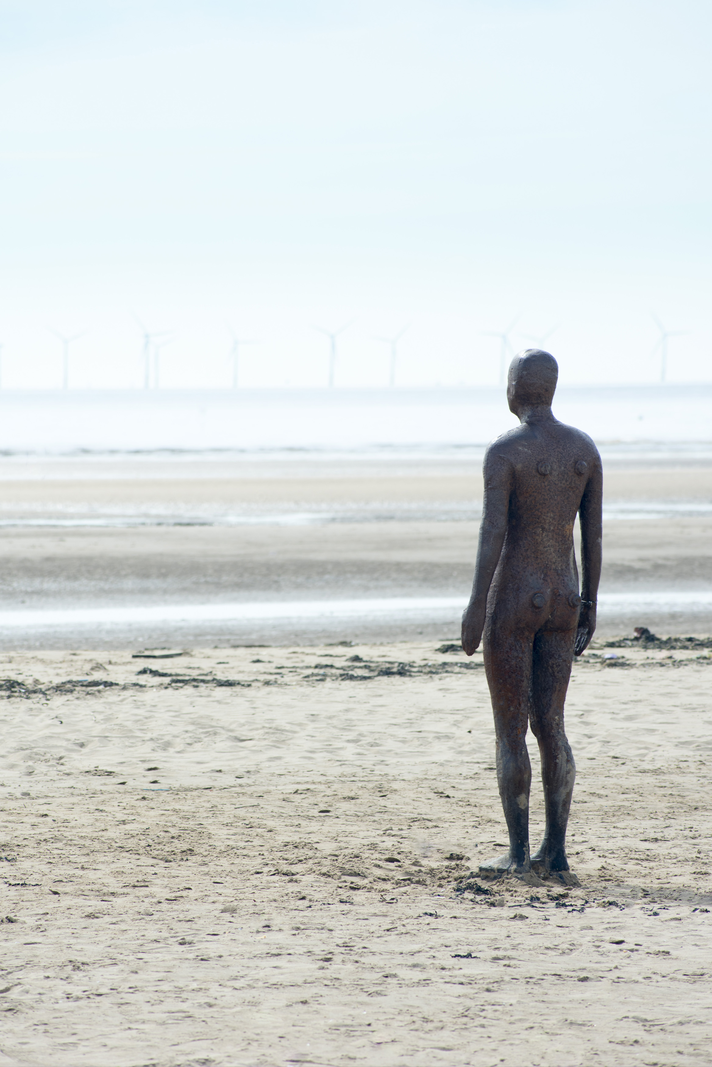 Another Place statue facing empty beach in Crosby, United Kingdom, with windmill power turbines in the far distance