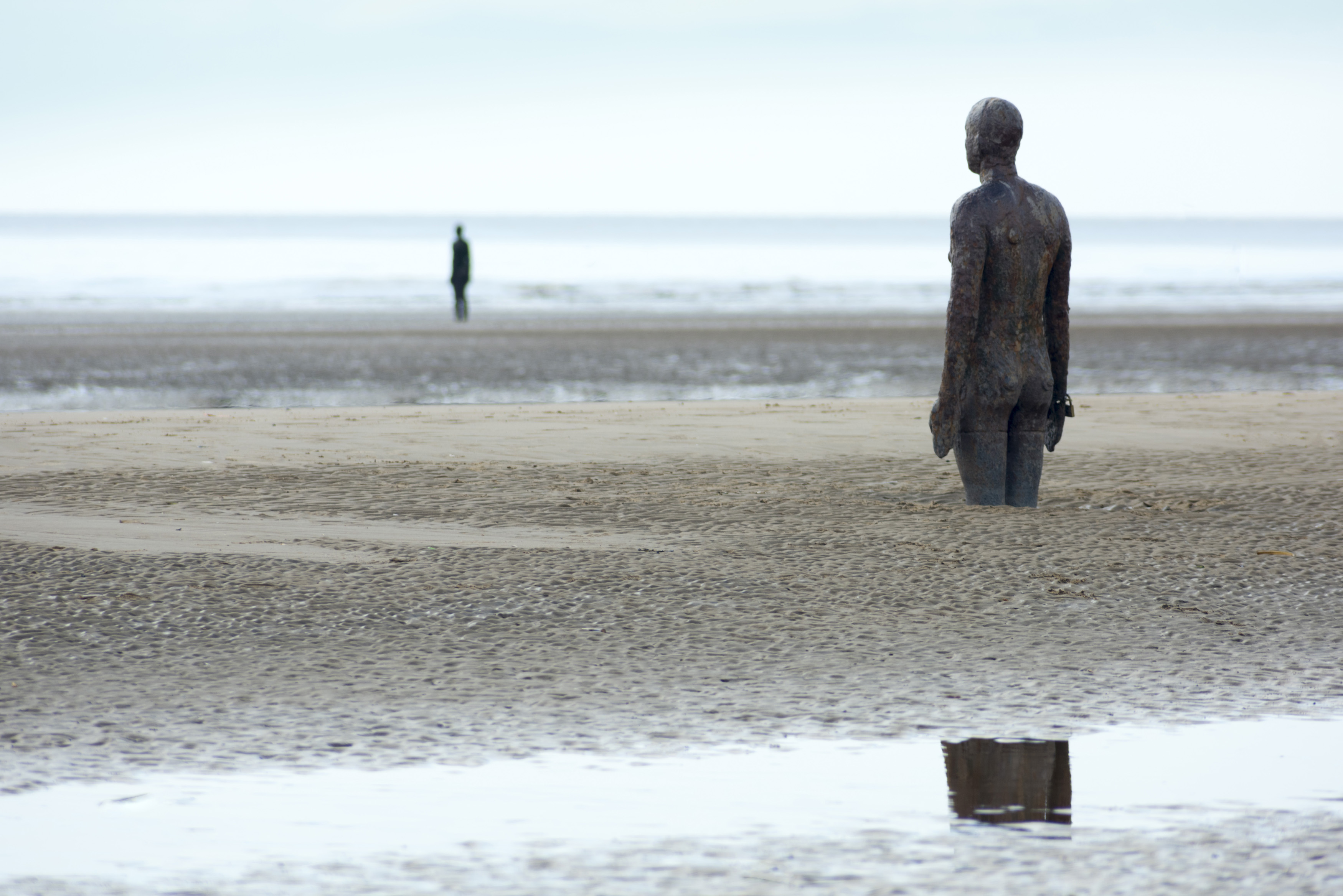 Pair of human shaped standing sculptures partially covered in sand at Crosby, UK under overcast sky
