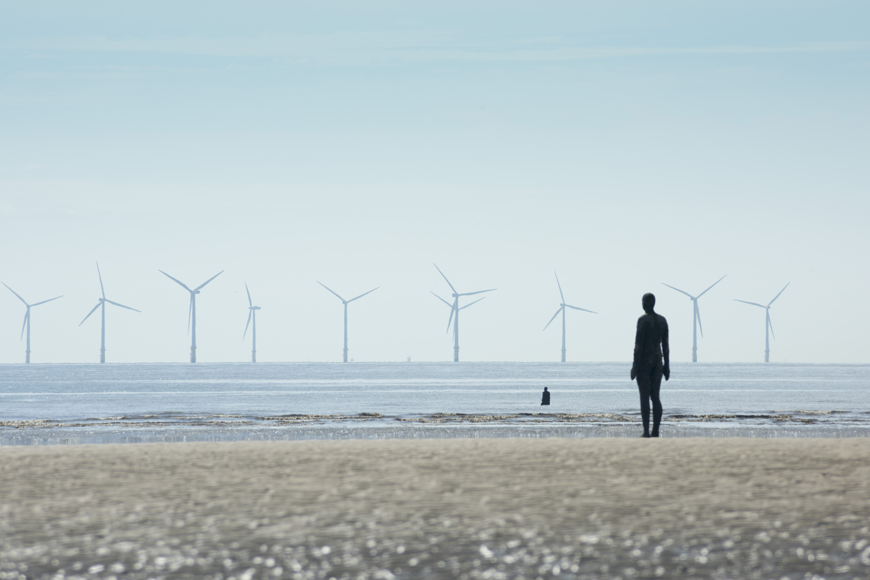 Row of multiple giant wind power turbines in background of Antony Gormley statue in Crosby, United Kingdom