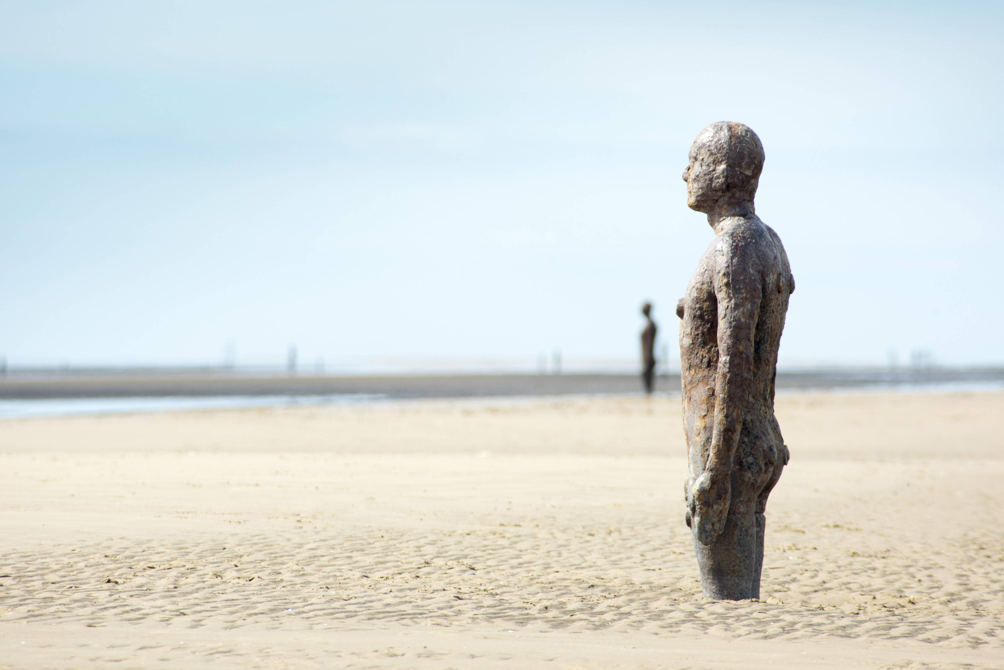 Cast iron statue in the sand on a beach facing out to sea - Another Place, by Antony Gormley at Crosby Beach, Liverpool UK