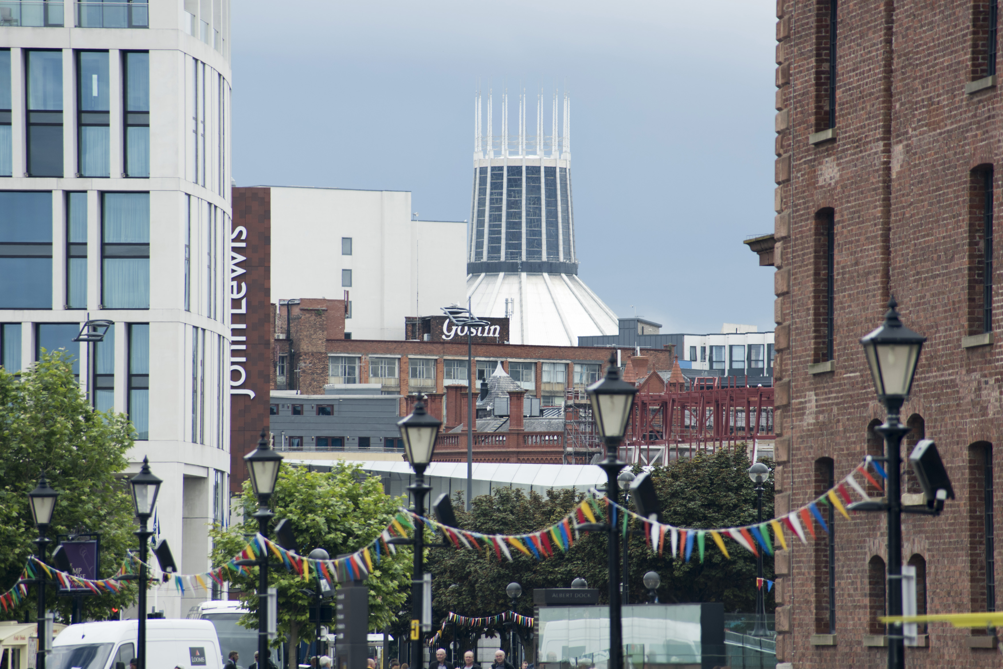 Row of six streetlamps connected with little flags under view of Liverpool Cathedral in the United Kingdom