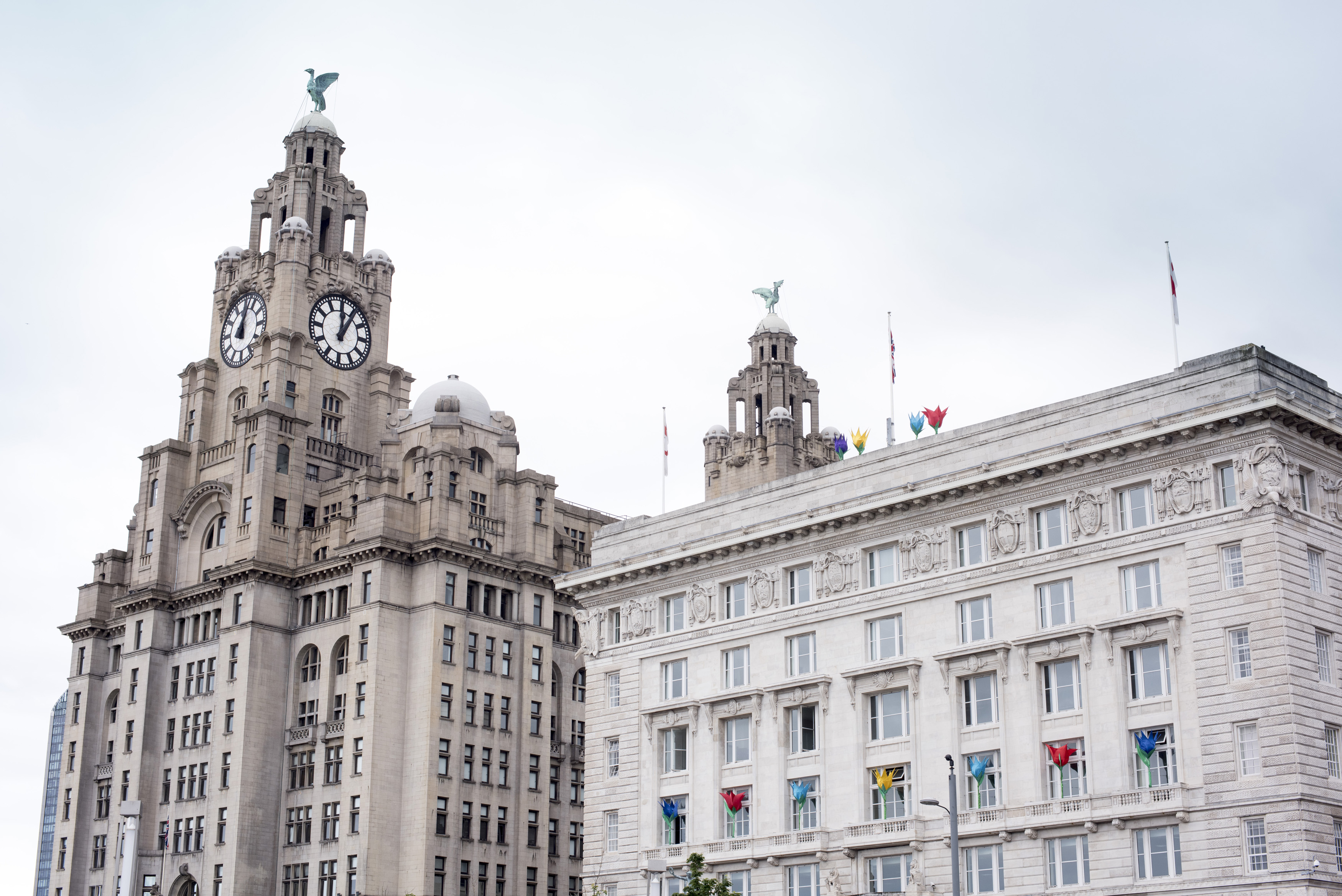 Liverpool Liver Building with famous clock tower and statues on top in the United Kingdom under overcast sky