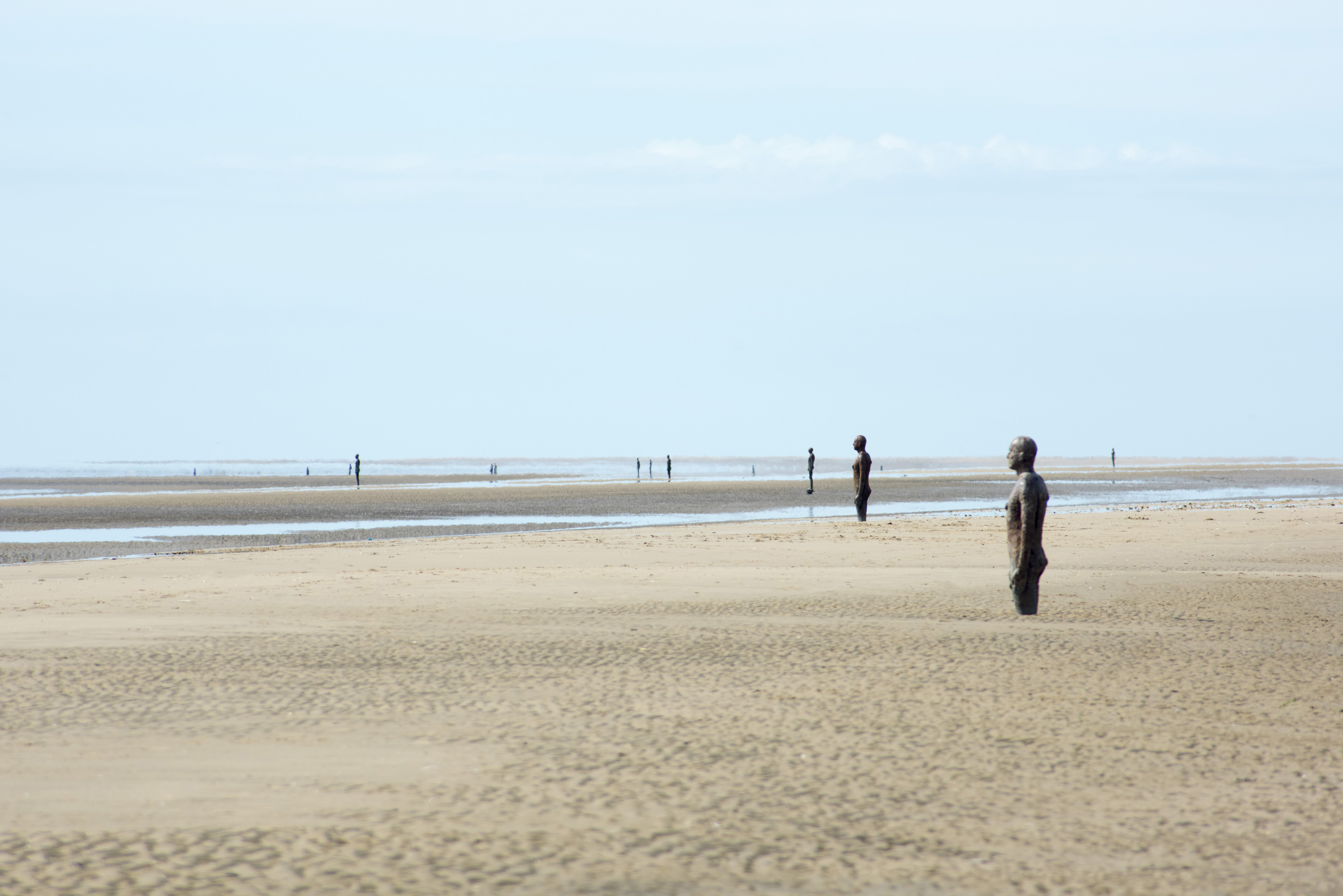 Another Place by Antony Gormley, Crosby Beach, Liverpool with 100 cast iron statues standing facing out towards the ocean