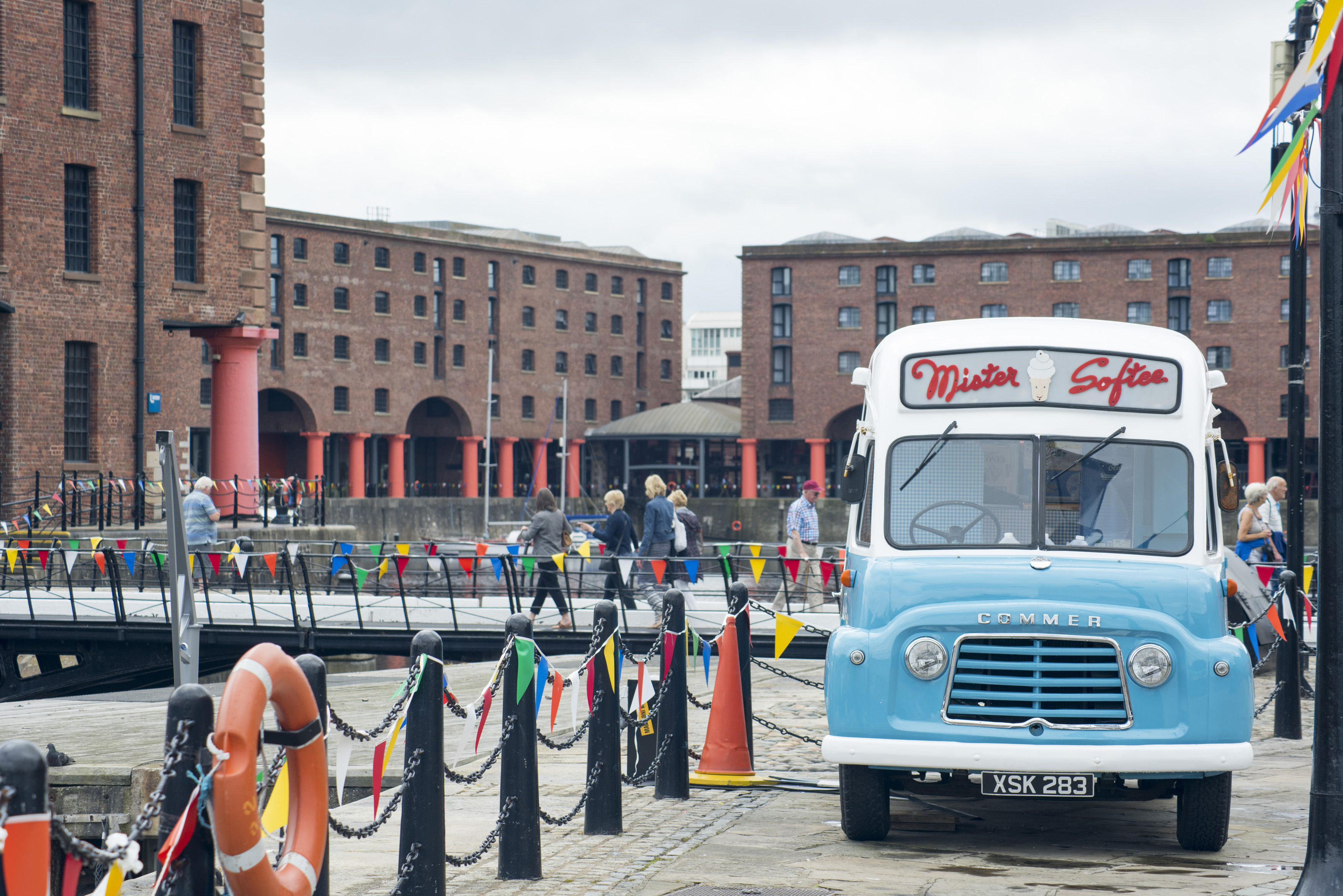 Old traditional ice cream van, Liverpool, England parked at the waterfront with people walking in the background