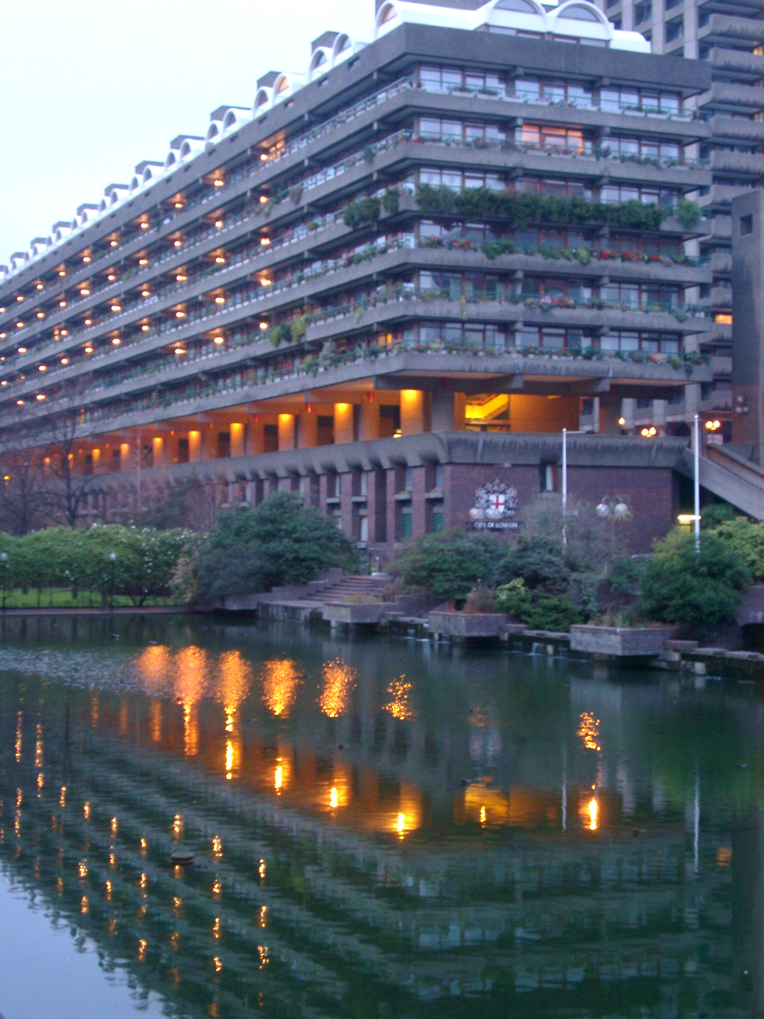 Barbican apartment block at dusk with the lights reflected in a pool below, London, England