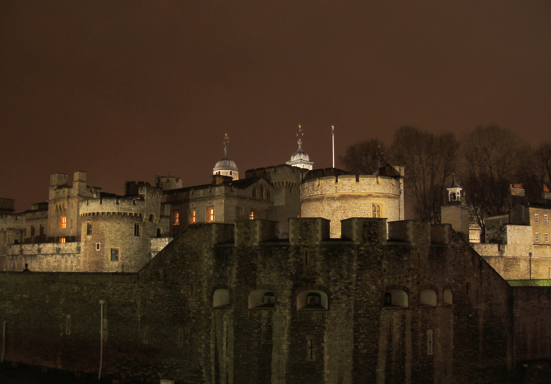 Night view of the iconic landmark Gothic structure of the Tower of London illuminated by lights showing the detail of the round towers