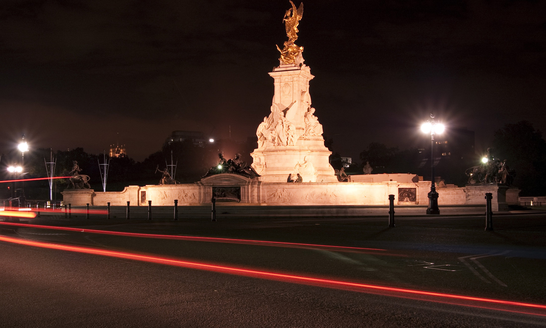 a night time view of the victoria memorial with gold statue of eros on top, located at the front of buckingham palace