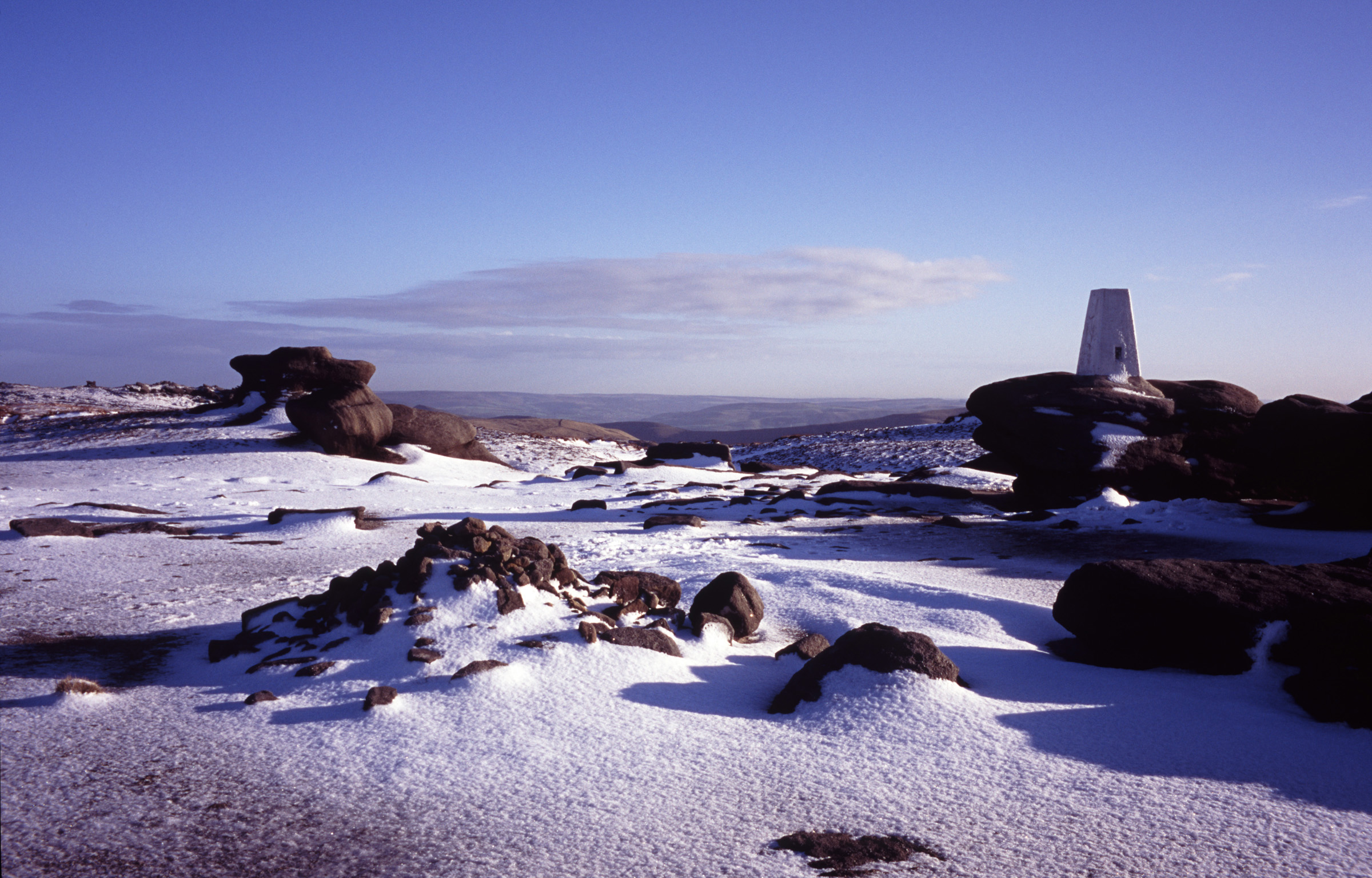 Picturesque view of the Kinder Scout moorlands in winter snow under a sunny crisp blue sky