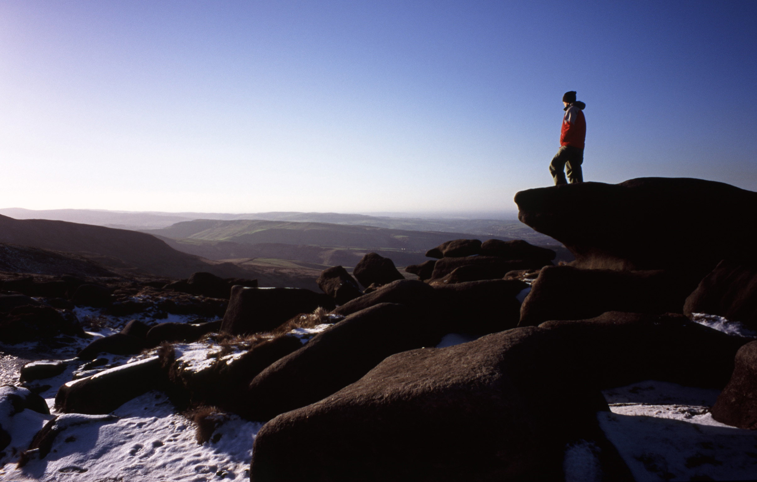 Man hiking on the Kinder Scout Plateau in winter standing on a rocky outcrop admiring the view over the moorlands in the Derbyshire Peak District
