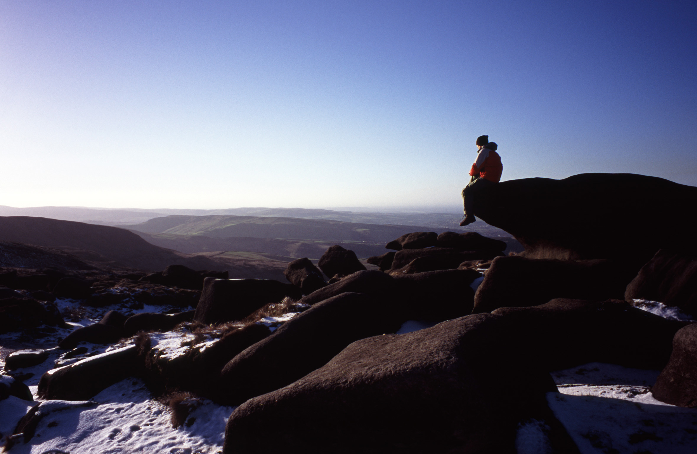 Person enjoying the tranquility of nature sitting on a rock on a snowy winter Kinder Scout, a moorland plateau and National Nature Reserve in the Dark Peak of the Derbyshire Peak District in England