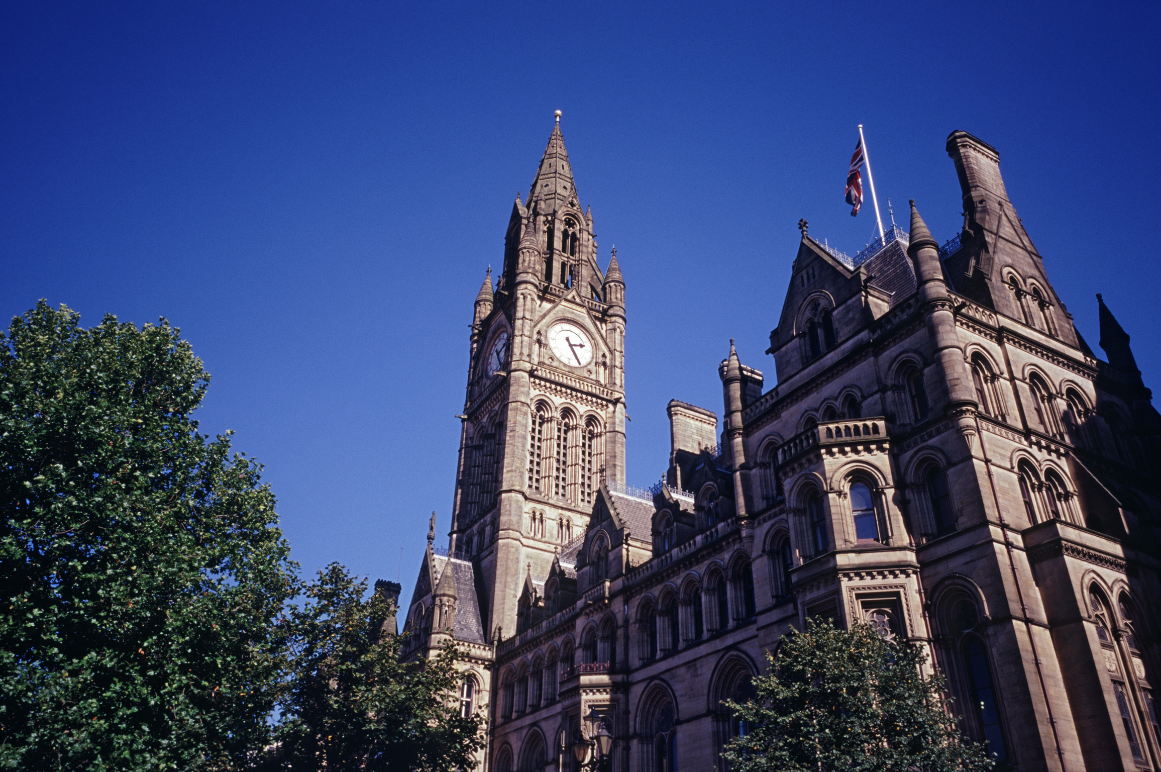 View of the exterior of the Manchester Town Hall with its Gothic revivaql architecture and ornate clock tower against a clear blue sunny sky