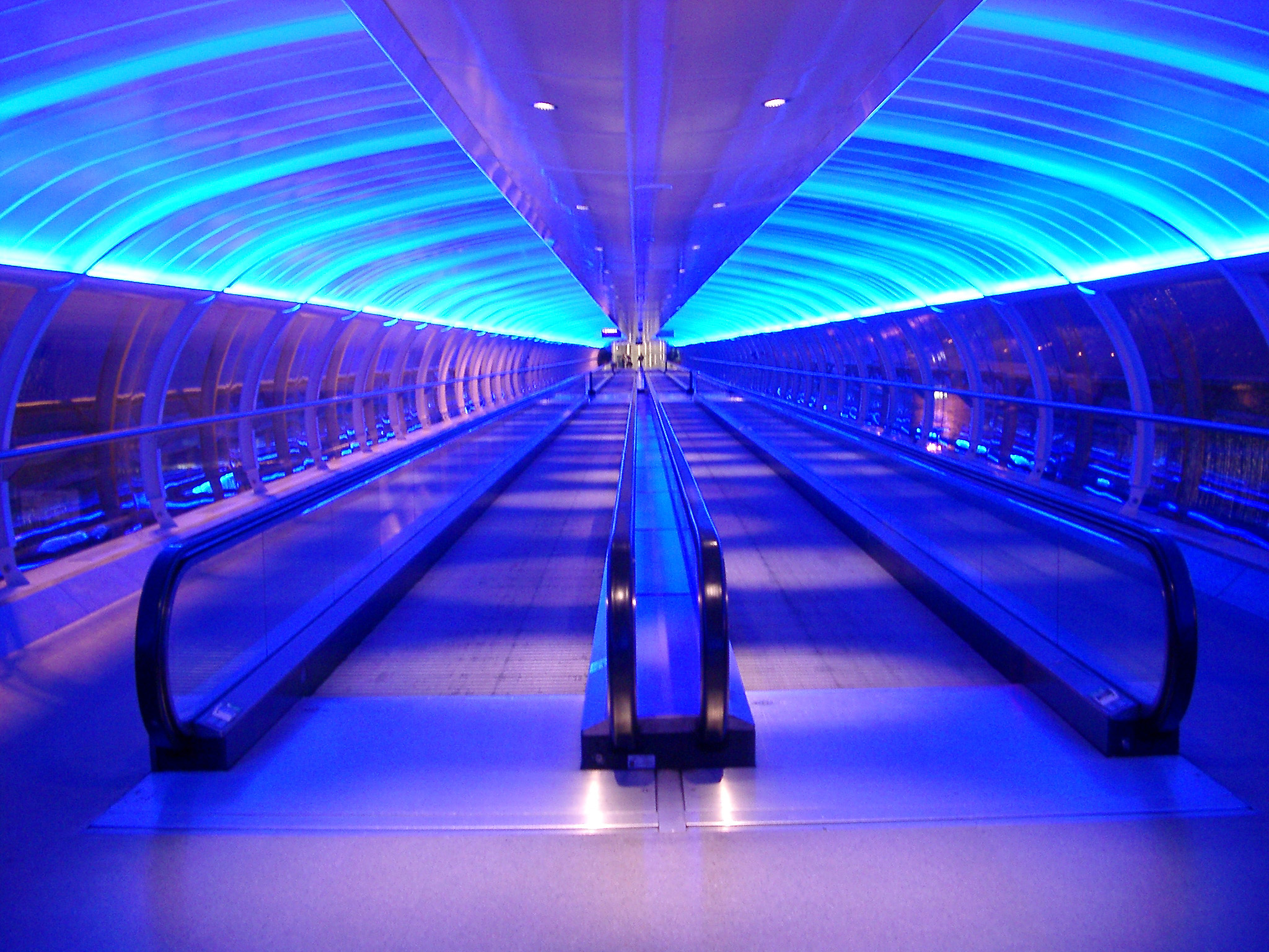 Interior of an airport walkway with two central moving travelators or passenger conveyor belts under a curved ceiling illuminated with blue lighting