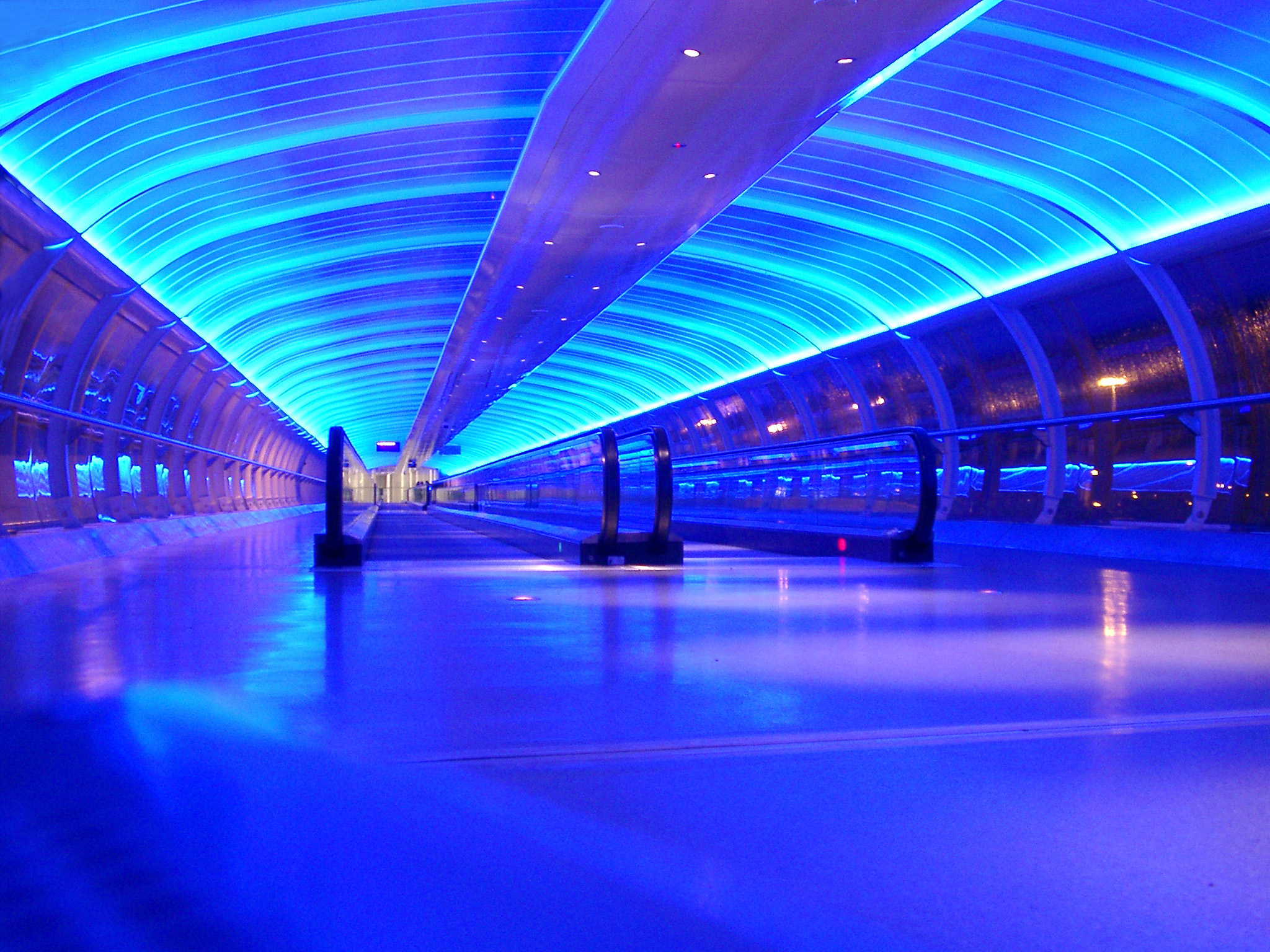 Interior of a blue airport sky bridge with travelators for pedestrians and overhead lighting in an arched ceiling