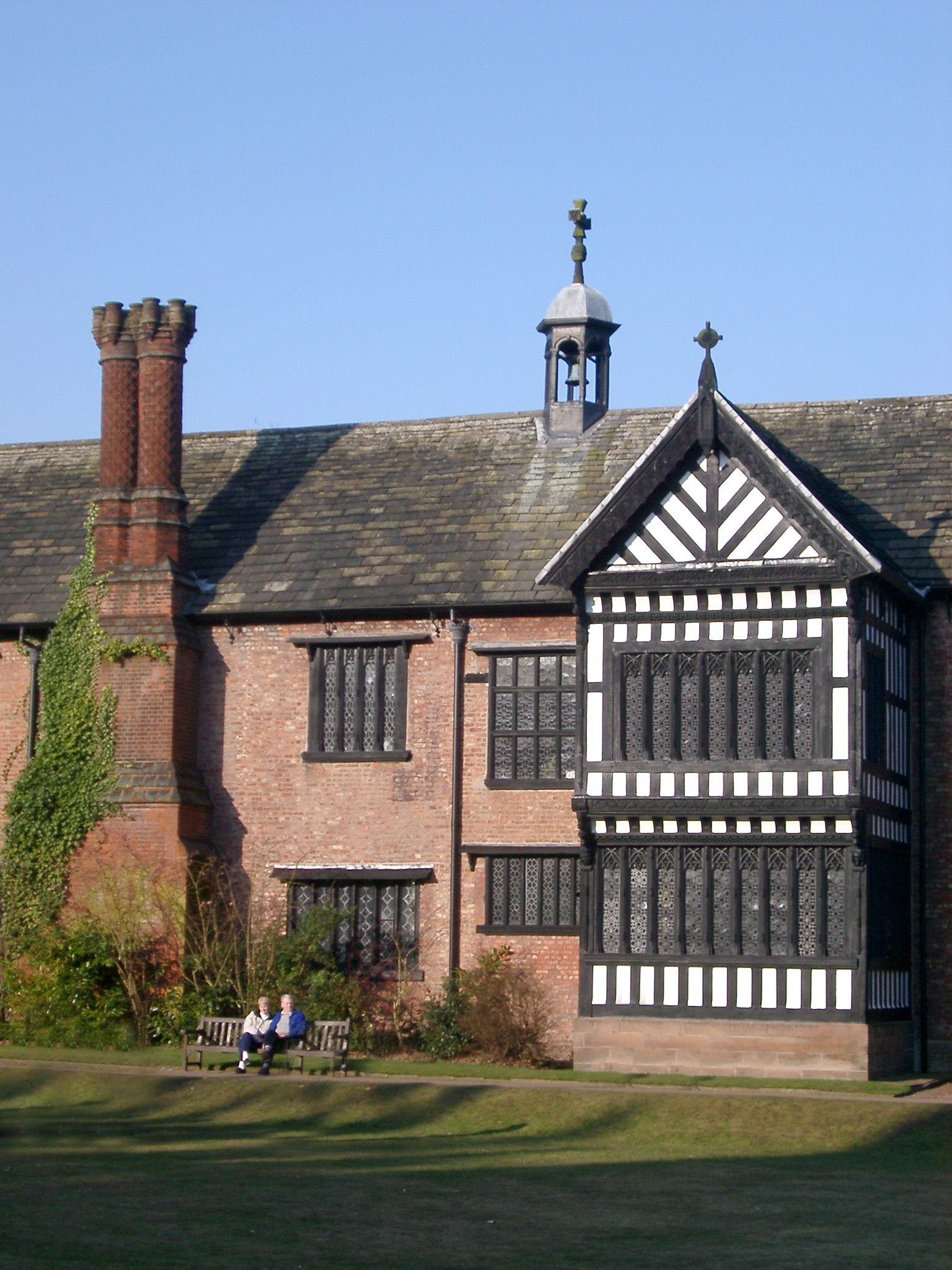 Visitors Sitting on the Bench in Front of the Bramhall Hall, a Tudor manor house in Bramhall, within the Metropolitan Borough of Stockport, Greater Manchester, England.