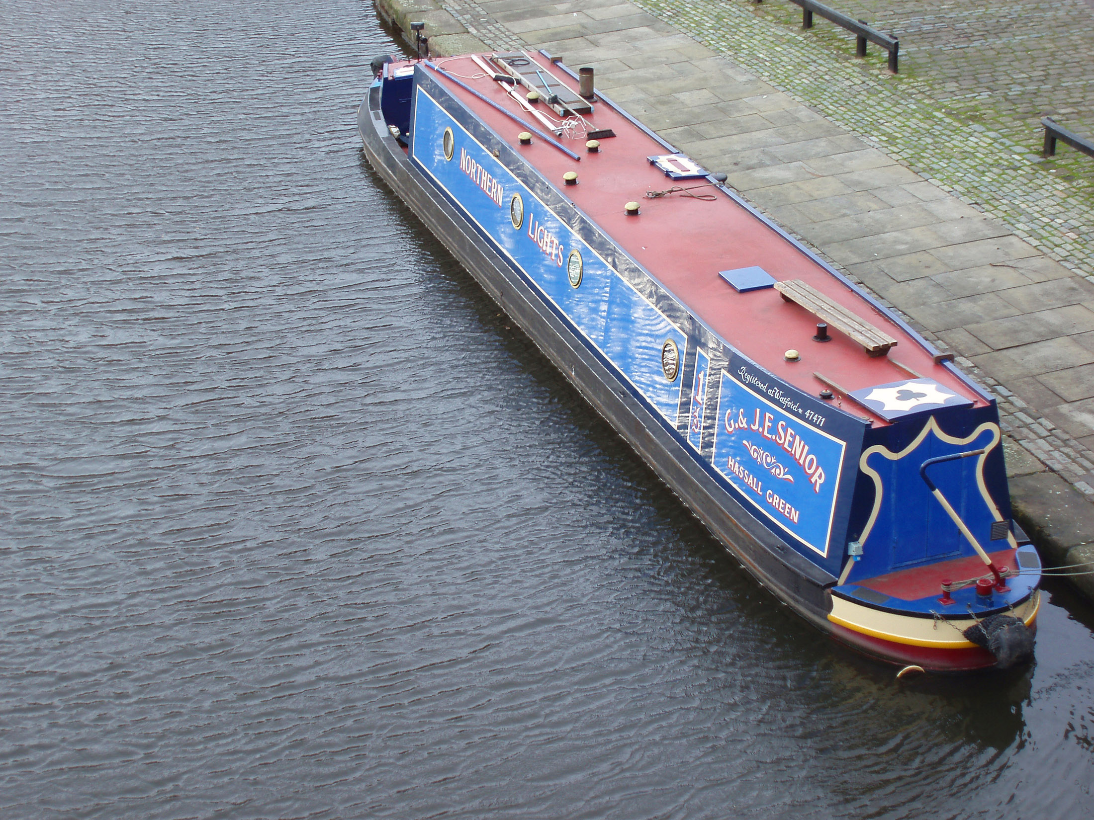High angle view of a traditional English canal narrow boat with advertising signs on the side moored at the side of the canal alongside a paved walkway