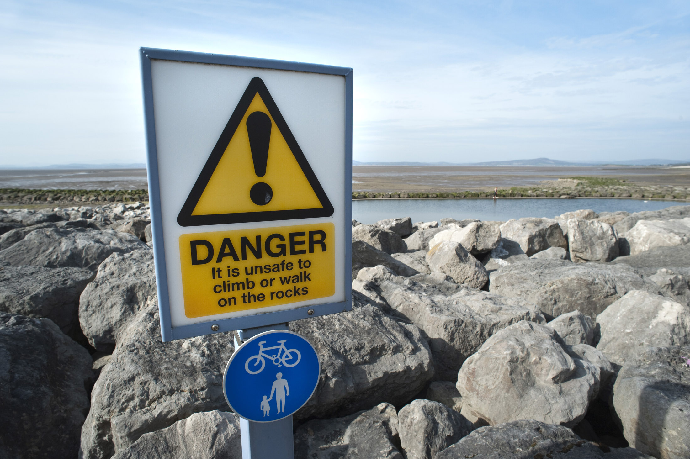 danger sign warning people not to walk on the moraine of boulders scattered along morecambe promenade to defend against the sea