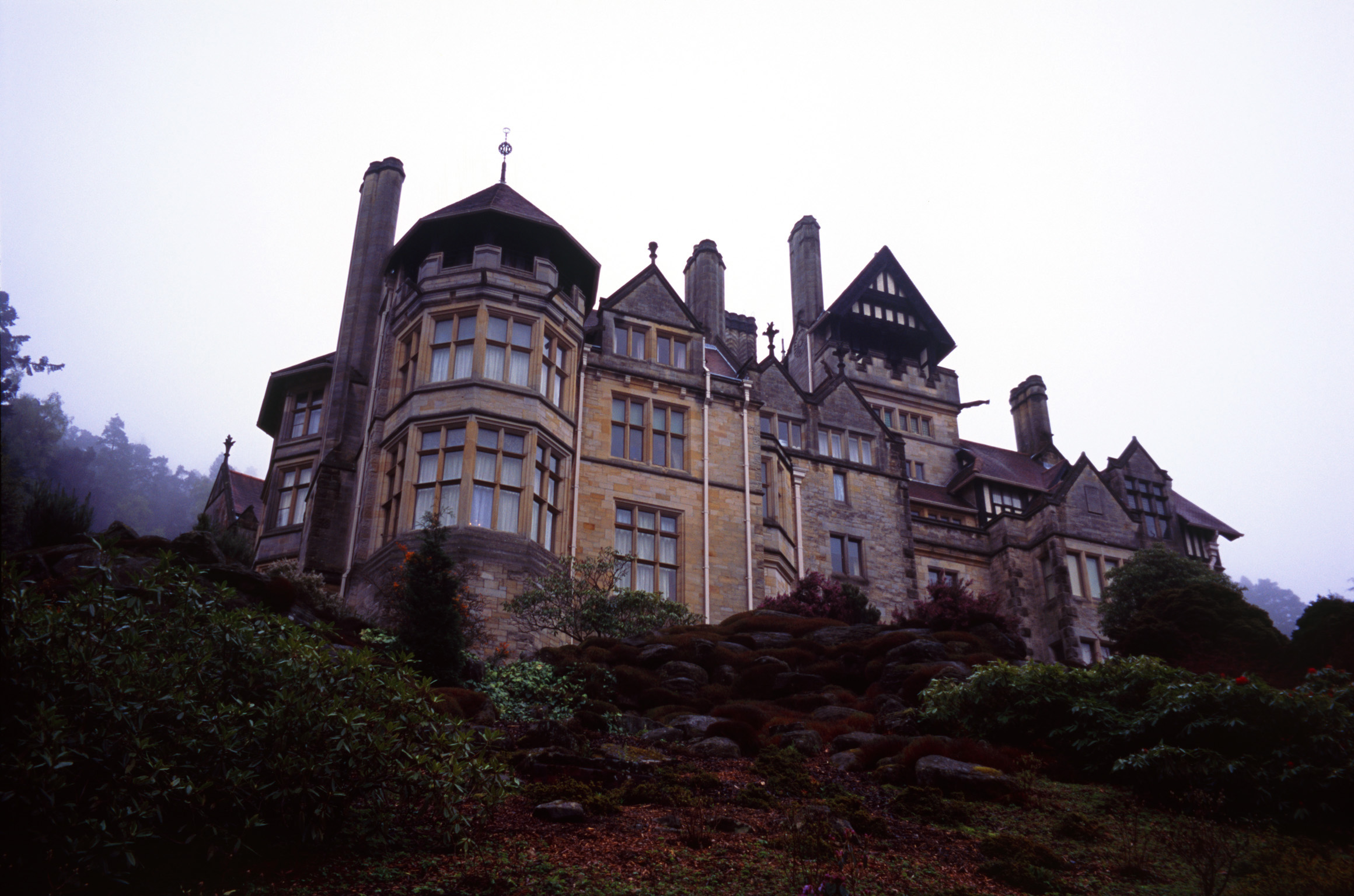 View on the skyline of the large stone facade of Cragside stately home, the first house to have electricity