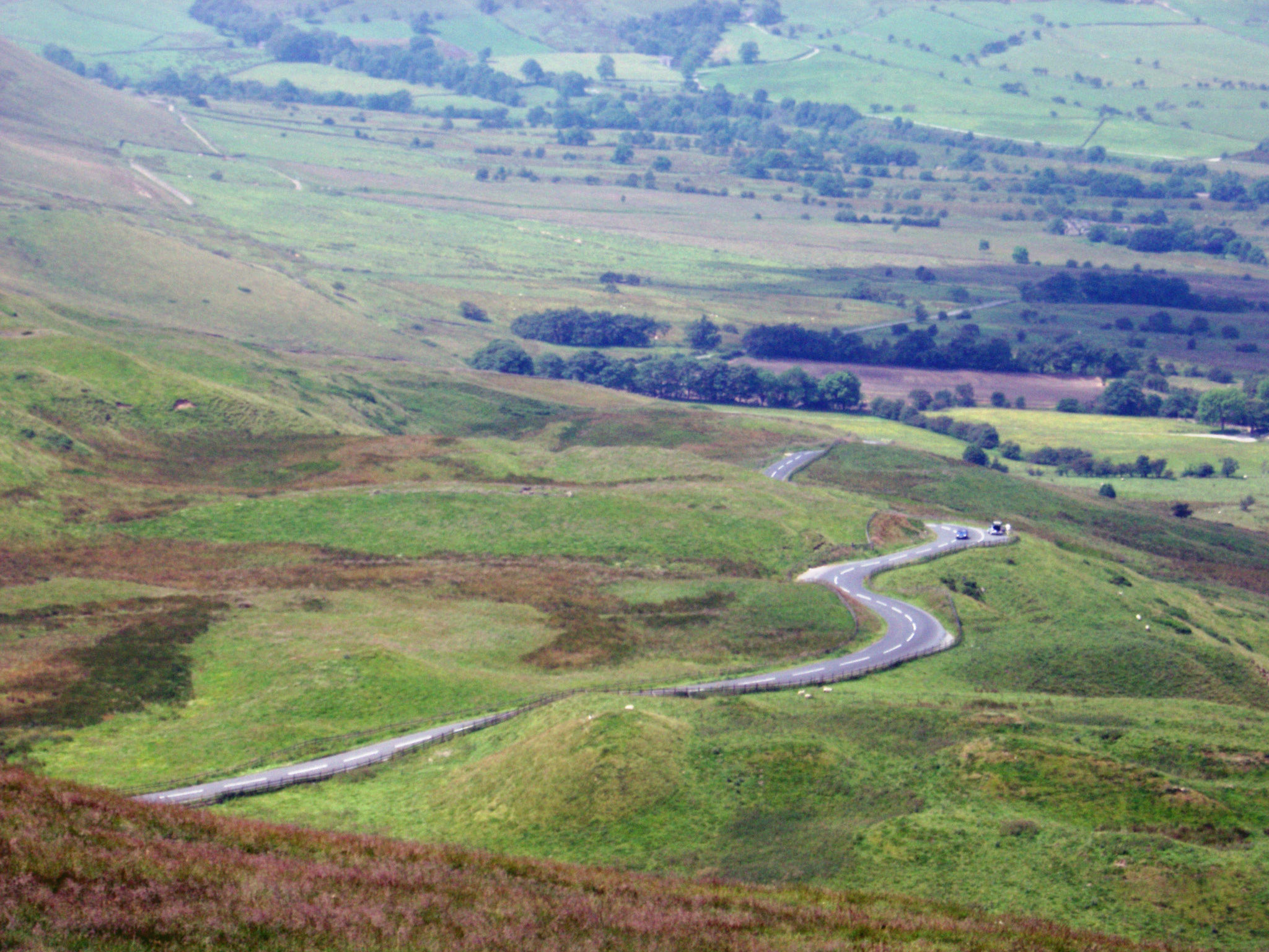Winding road snaking through lush countryside near Edale in the Dales, Peak District, Derbyshire
