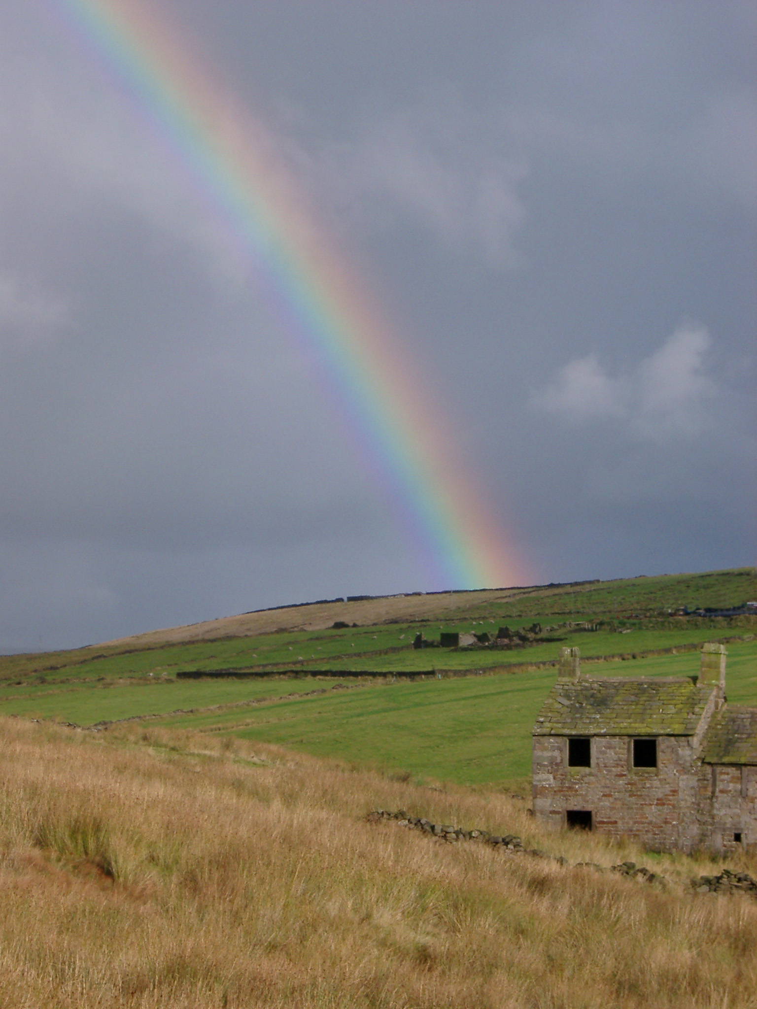 Ruins on an old farm house on a grassy moorland, Captured with Rainbow in the Sky.