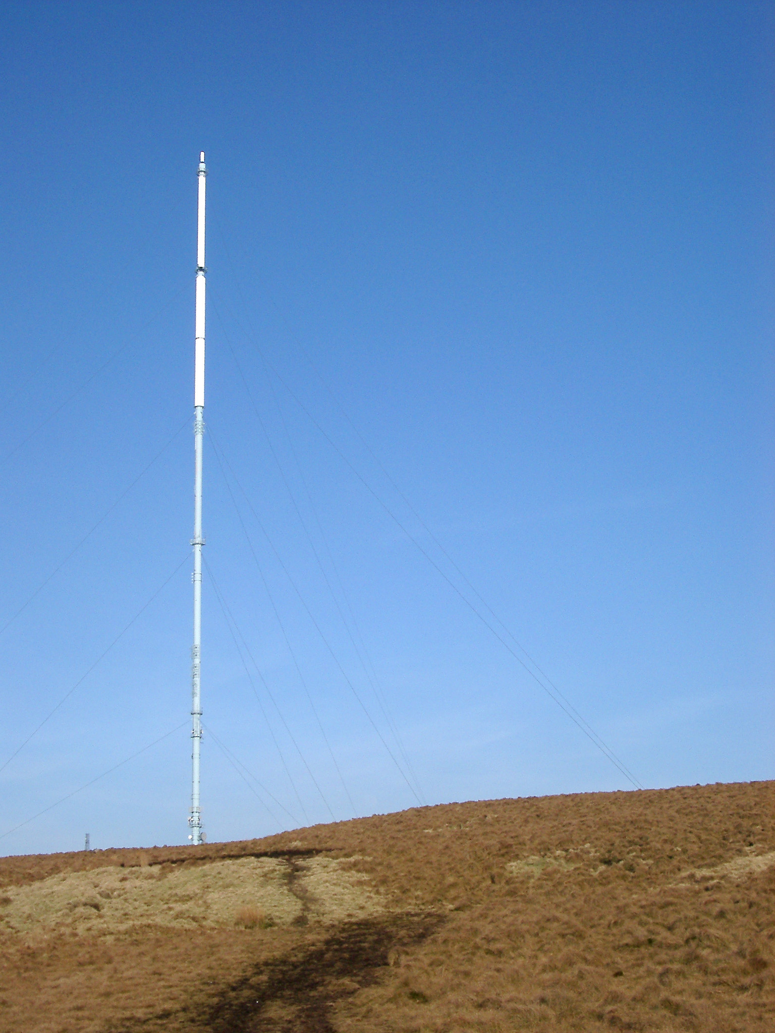 Tall communications transmitter on a winter hill top against a clear sunny blue sky