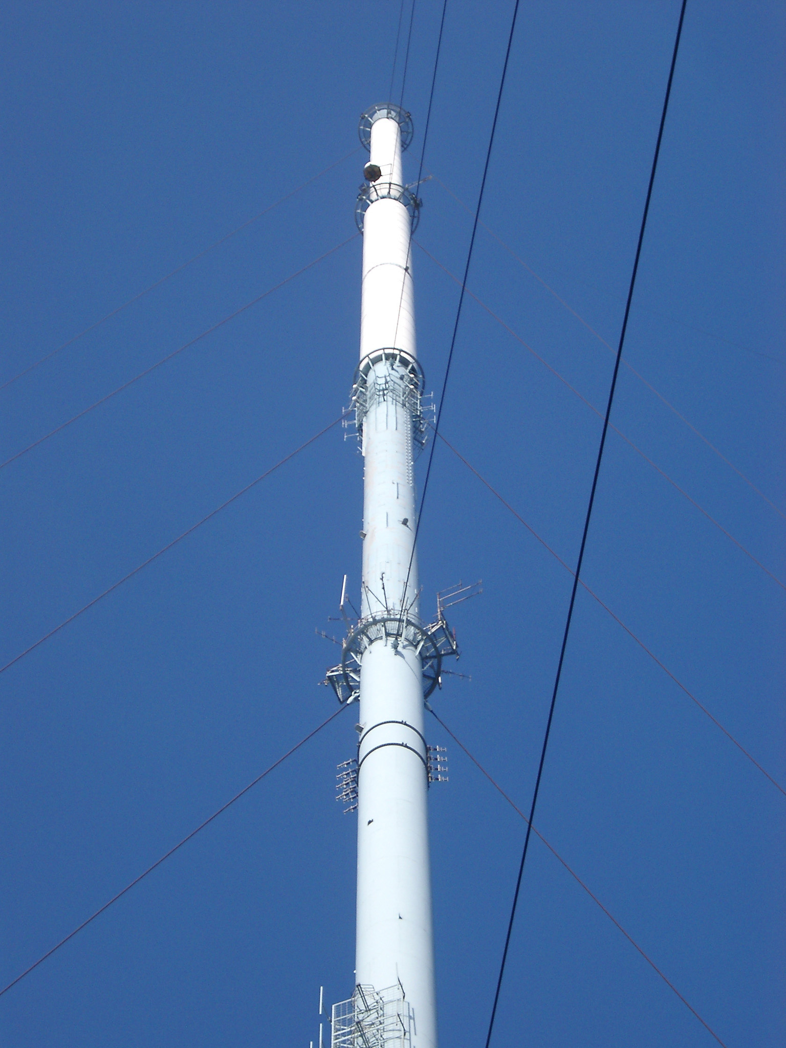 Tall white television transmitter tower on the West Pennine Moors at Winter Hill against blue sky