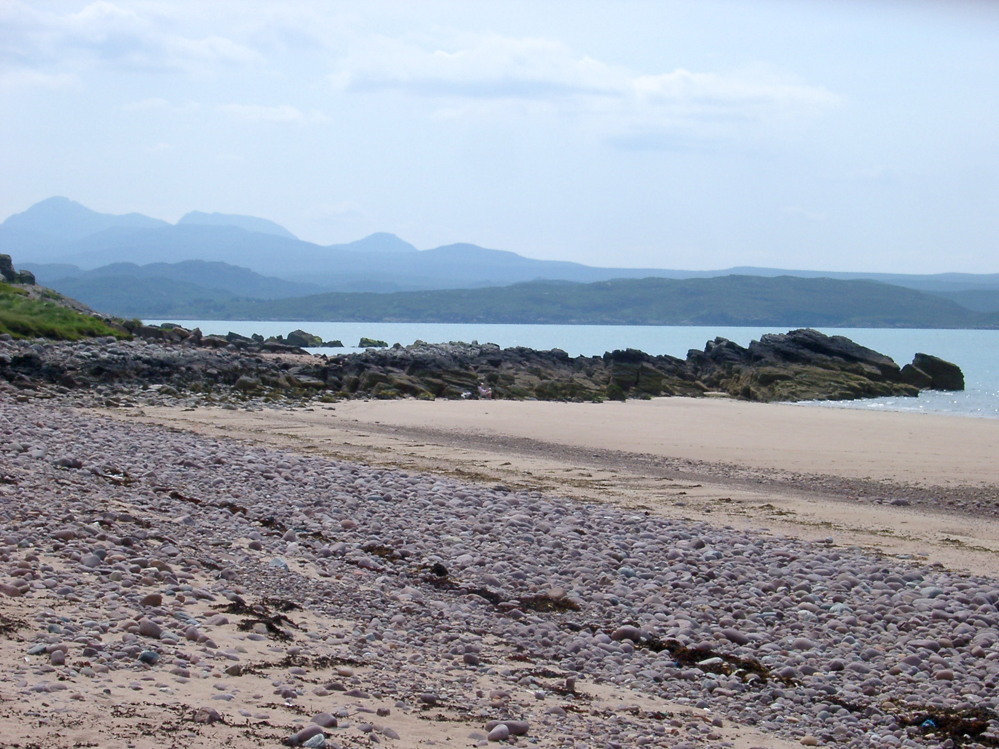Scottish beach landscape at Gairloch with golden sand and a rocky shoreline against a mountain backdrop on an overcast sunny day