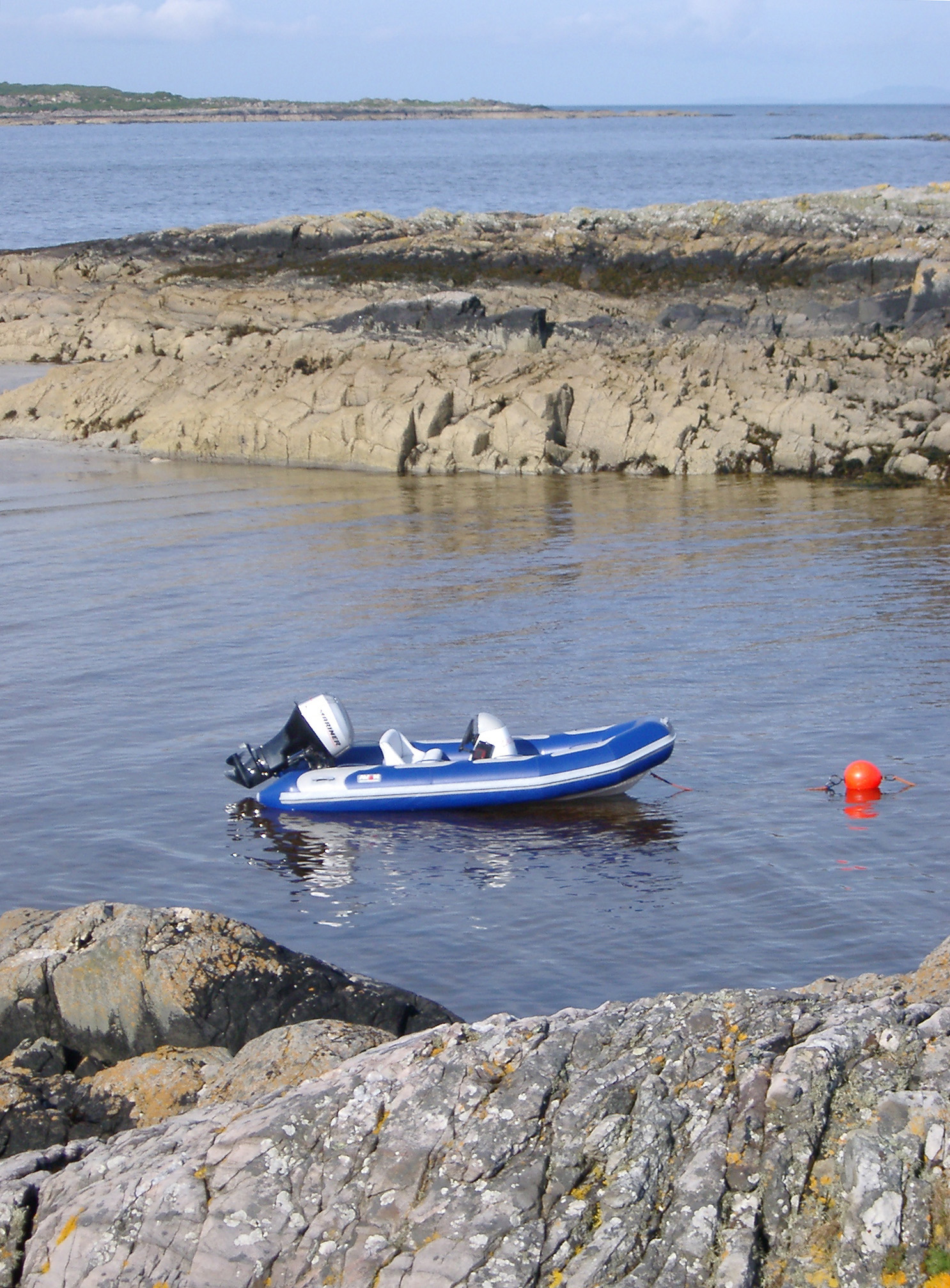 Rubber dinghy moored to a buoy in a coastal inlet between rock formations for fishing and water sport