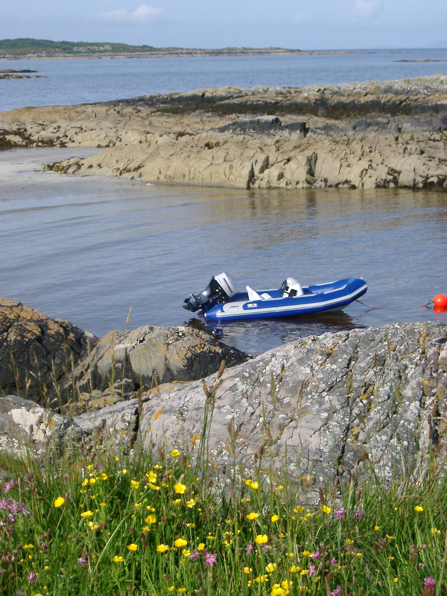 Inflatable rubber dinghy with a small outboard engine moored to a buoy in a rocky coastal inlet in Maillag, Scotland