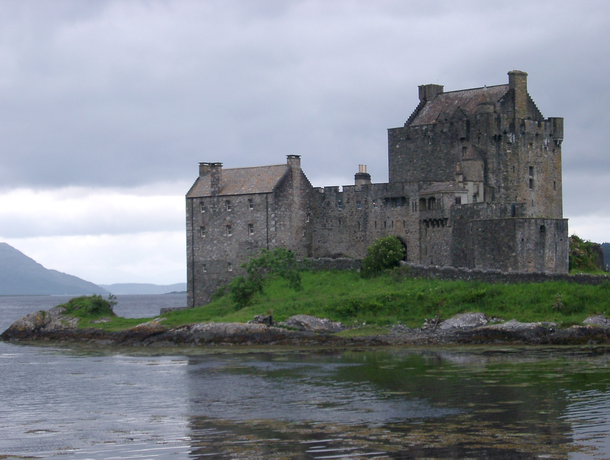 Eilean Donan Castle, Scotland standing on its island in the centre of Loch Duich on a calm cloudy day