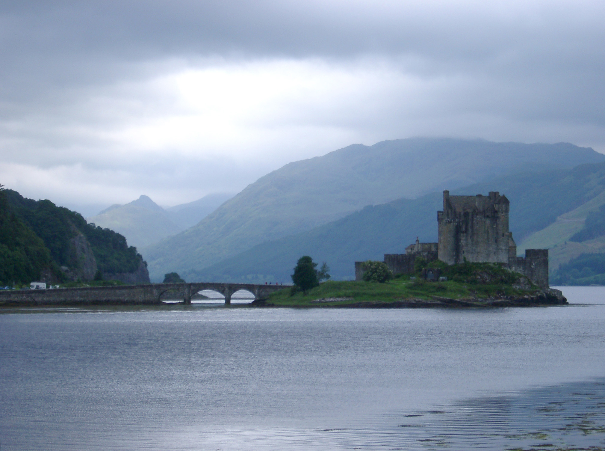 Eilean Donan castle on an island in Loch Duich, Scotland with its old arched bridge connecting it to the mainland