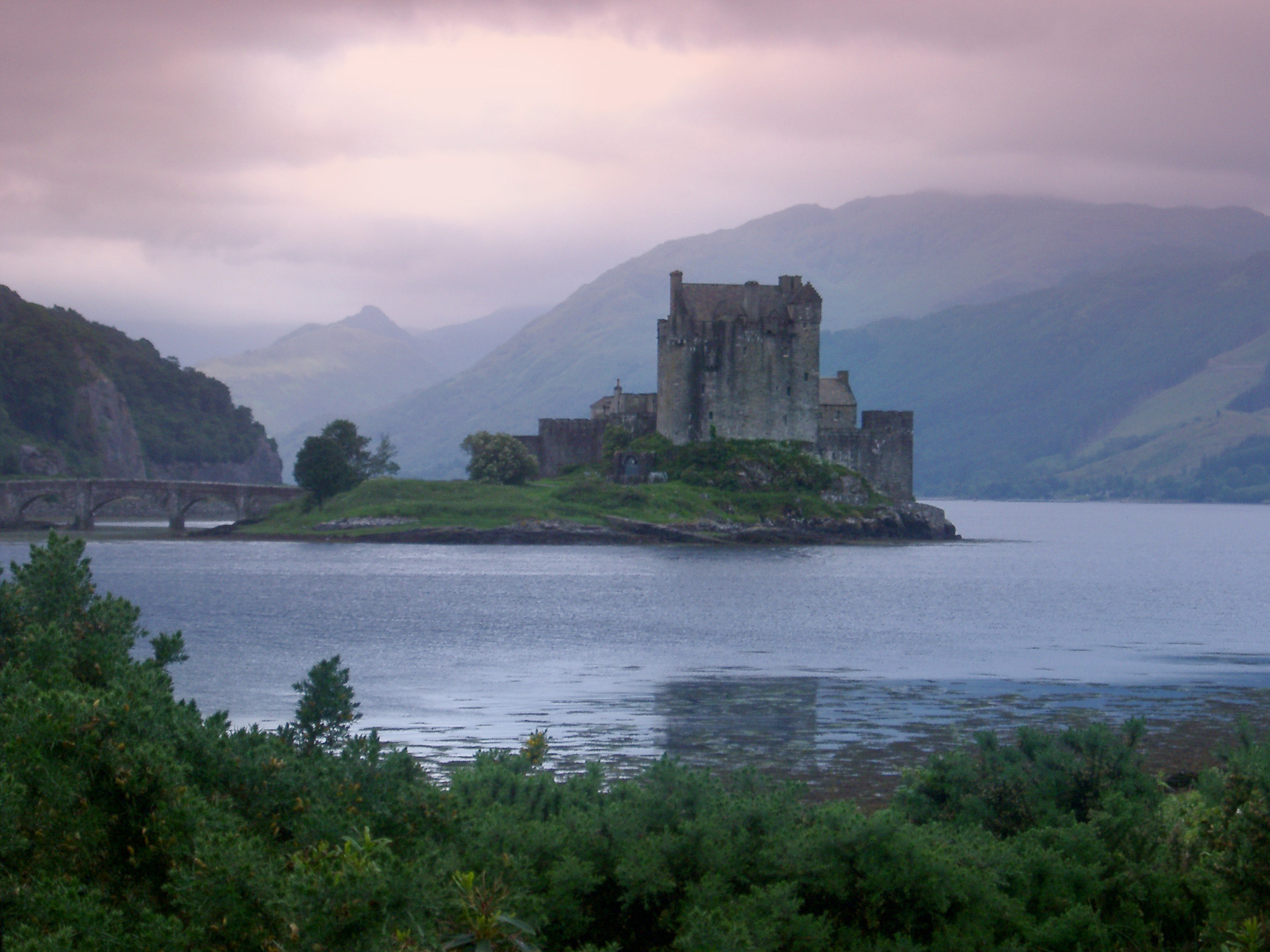 Scenic atmospheric panoramic view of Eilean Donan Castle, Scotland standing on its island in the centre of Loch Duich on a calm cloudy day with a feint mist and purple tint to the sky