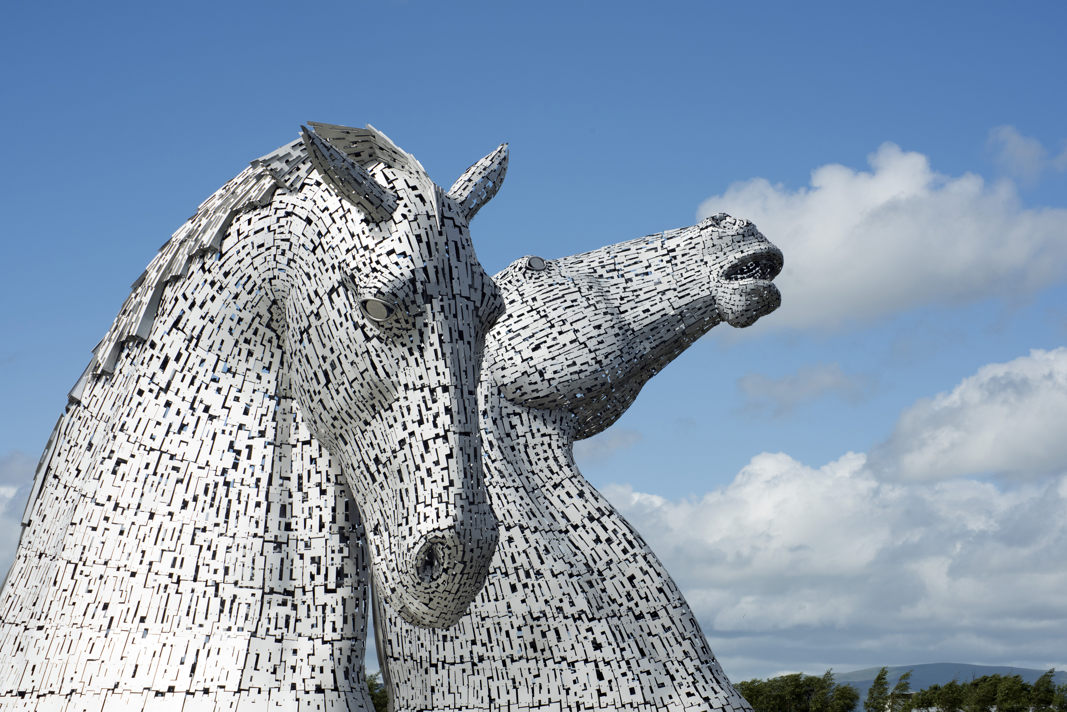 The Kelpies pair of horse head sculptures in Falkirk Scotland under summer sky with scattered clouds and copy space