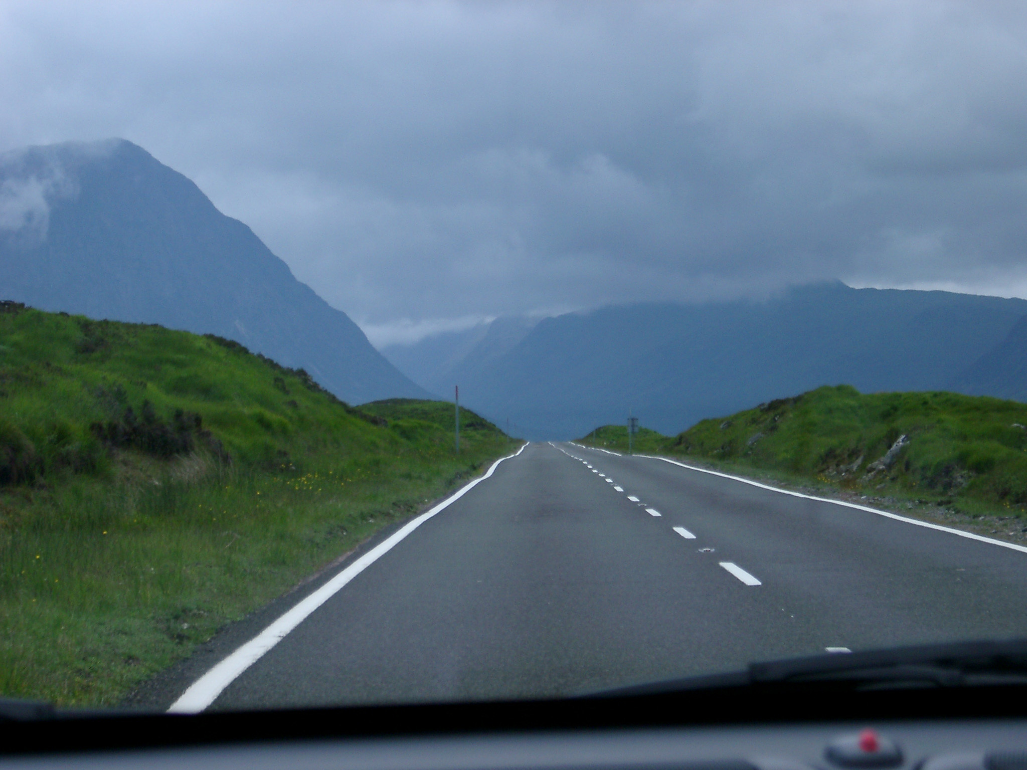 View through the windshield of a car of a tarred road through the Scottish highlands with high mountain peaks on a cold overcast day