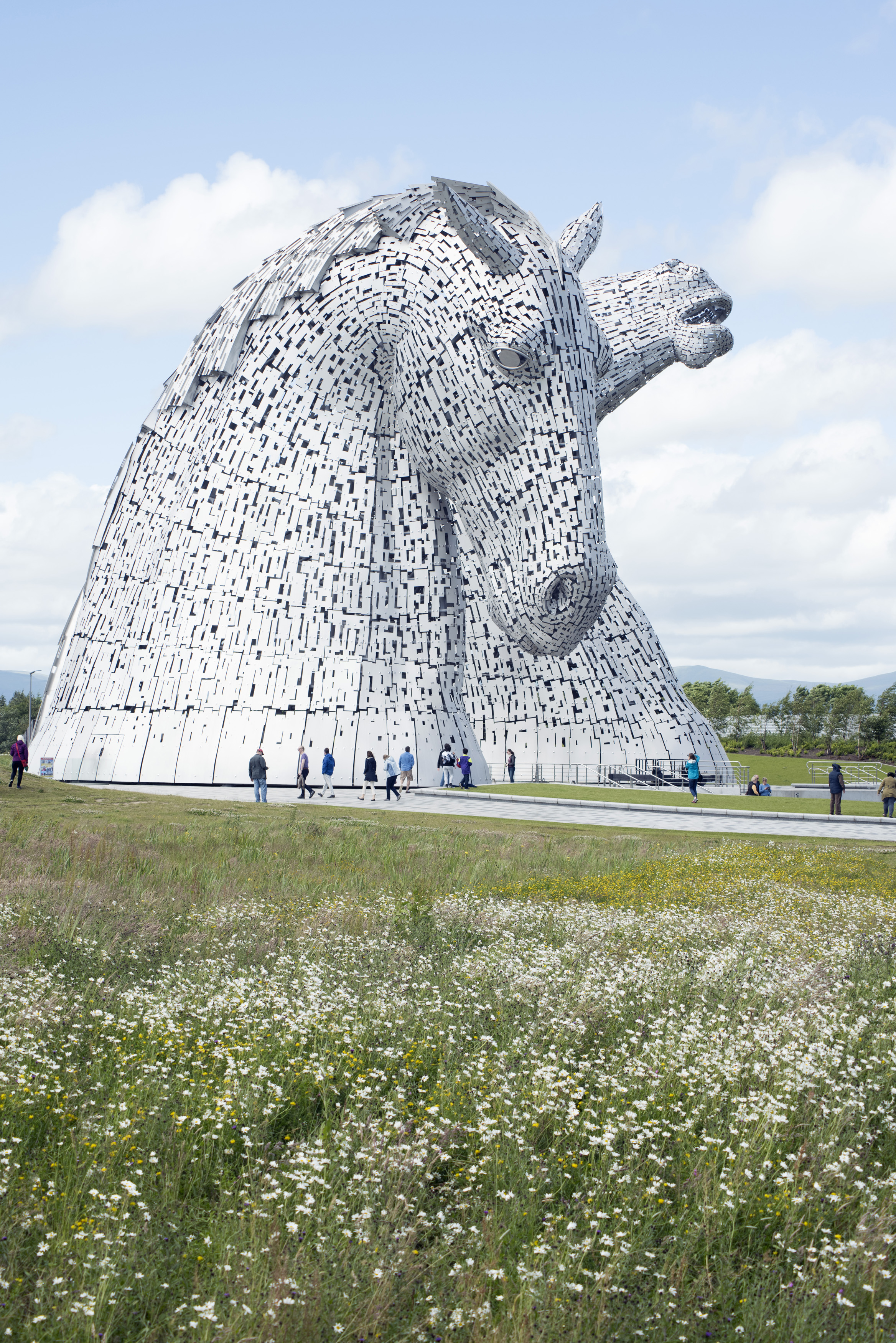 Kelpies horse monuments surrounded by scattered clouds in grassy field at Falkirk, Scotland