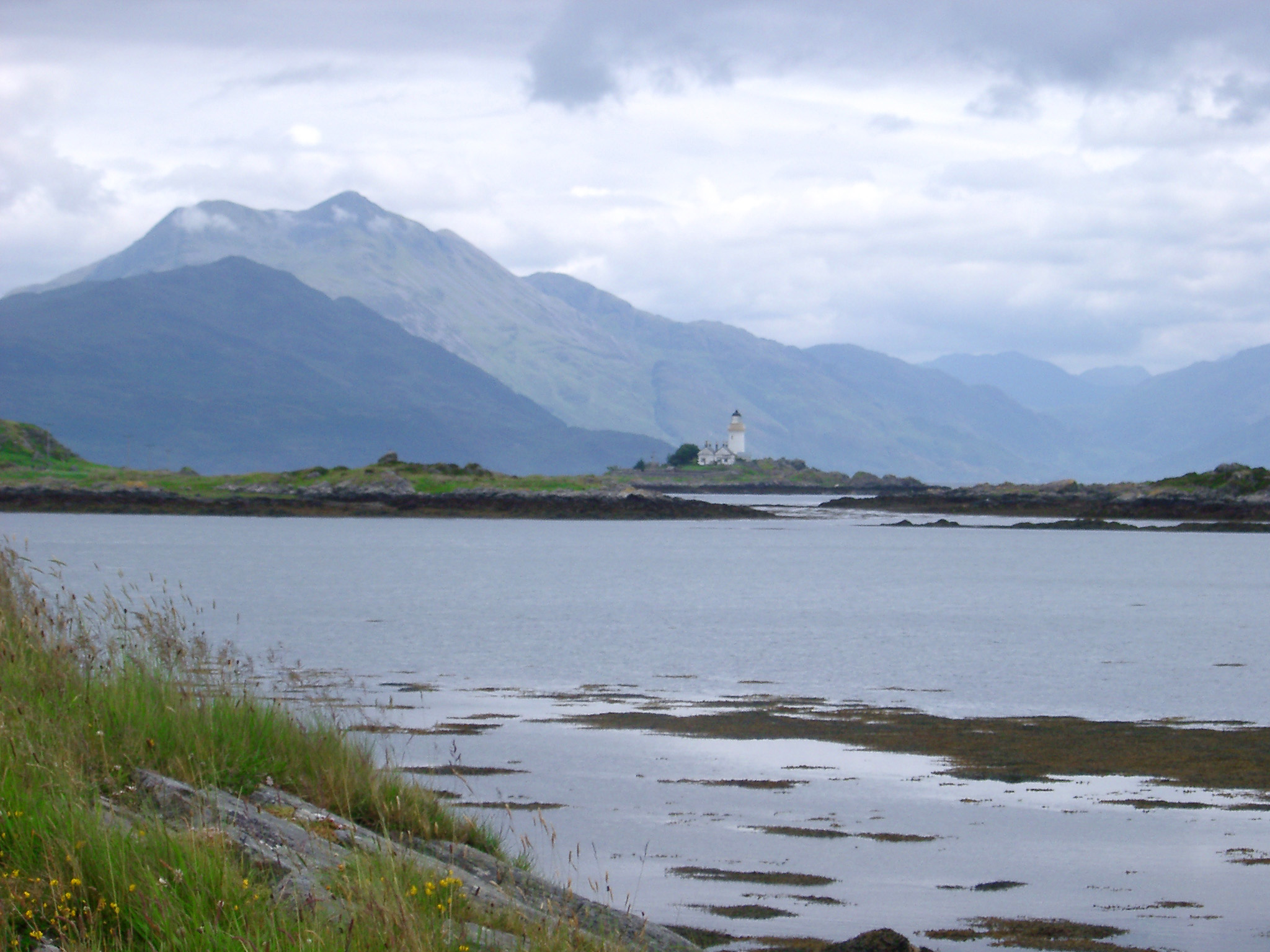 Scenic view across the water of the Isle of Skye and its lighthouse below mountain peaks on a sunny cloudy day