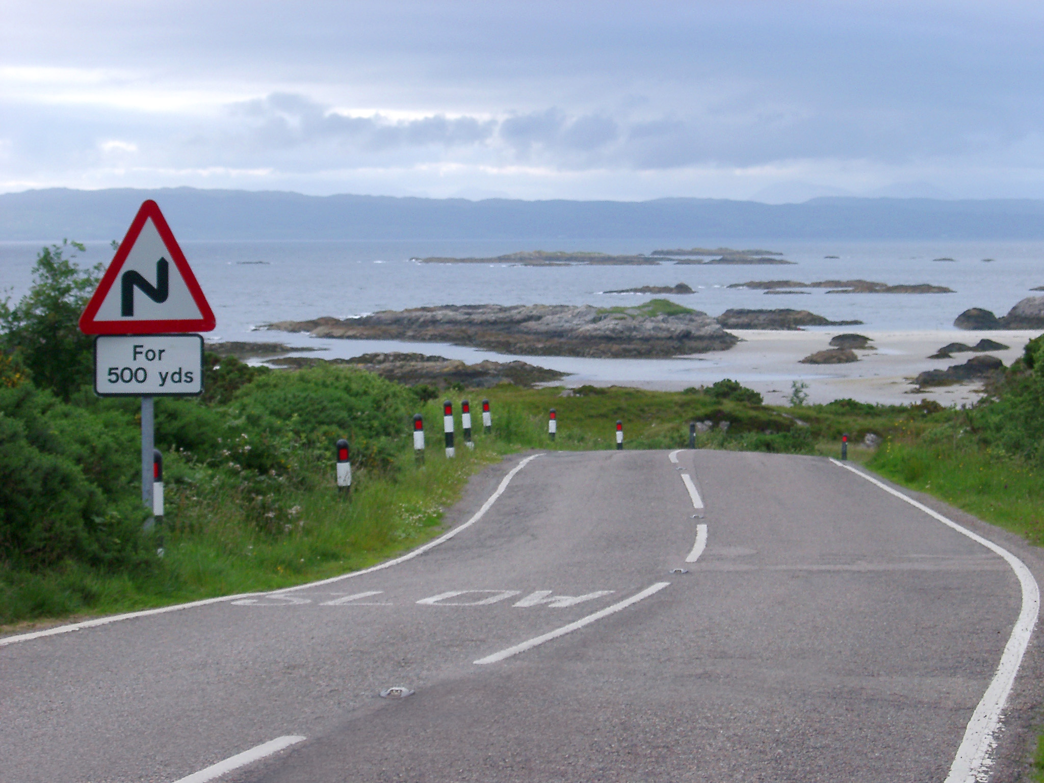 Scottish roads showing a curving bend with a hazard sign warning of bends for 500 yards along a section of the coastline