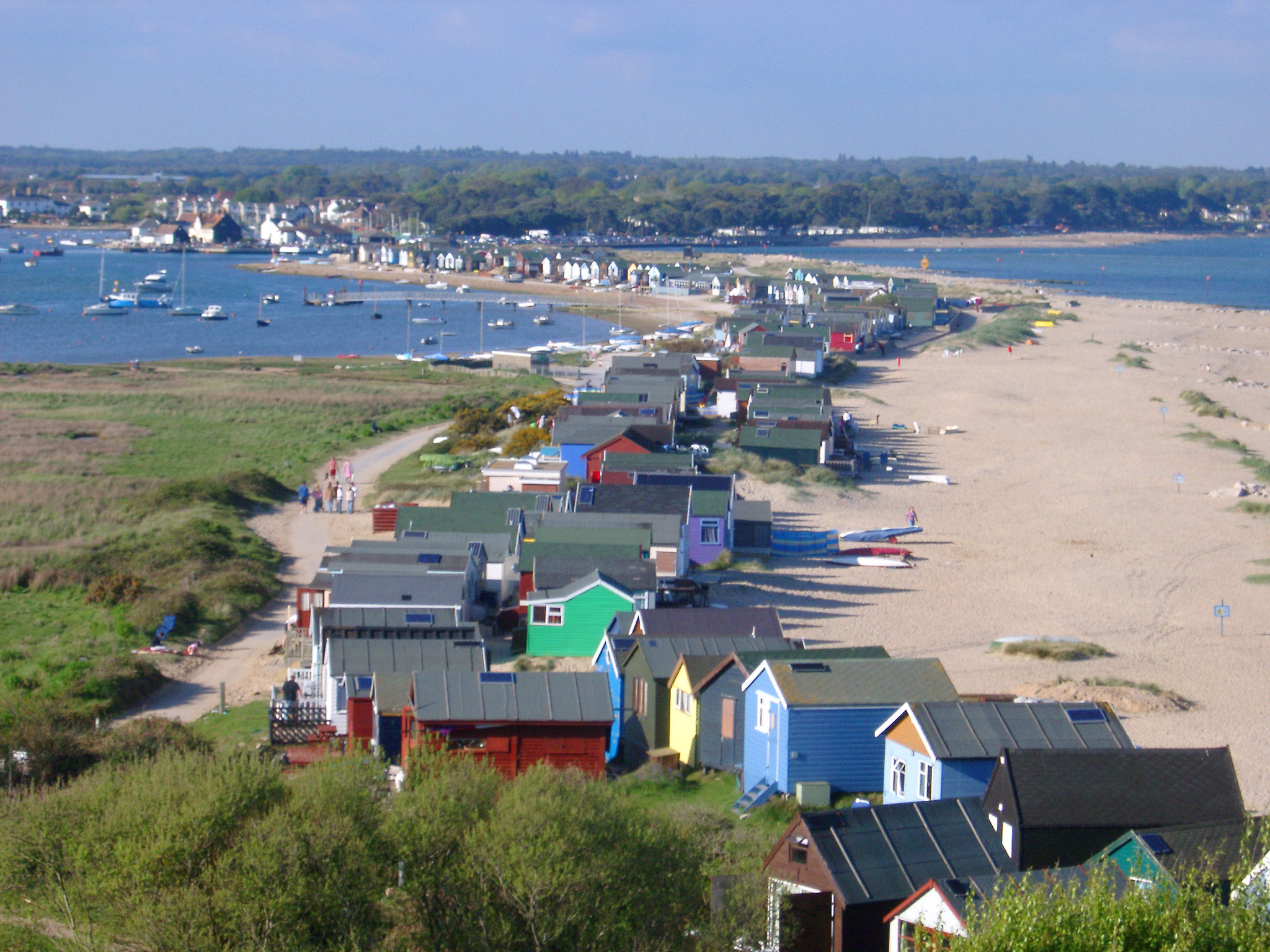 Row of colorful beach huts or cabins for vacations and getaways lining the Dorset seashore, high angle landscape view
