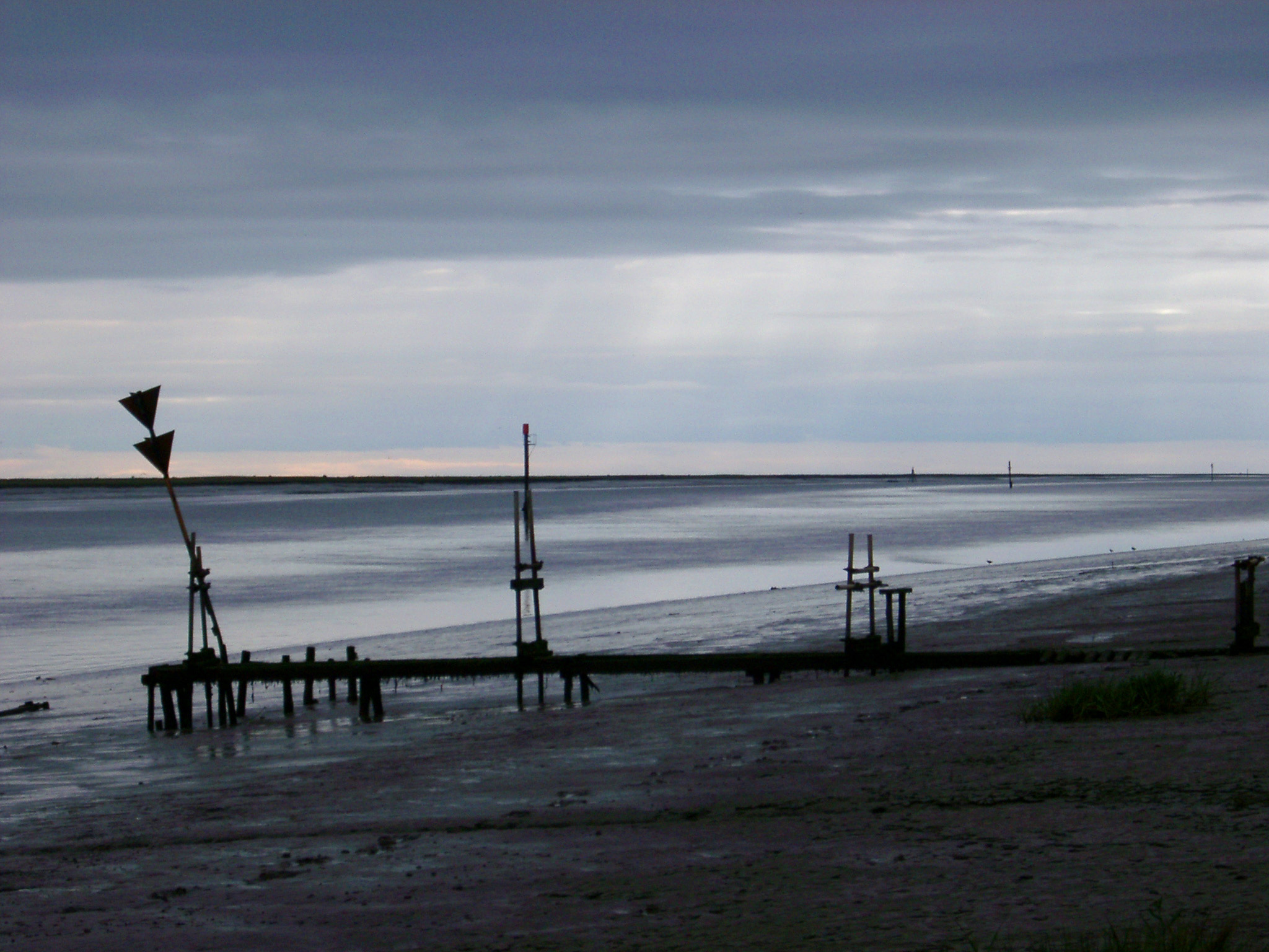 Dark atmospheric landscape of a marine estuary on an overcast stormy day with a silhouette of a small jetty and warning signs on the beach in the foreground