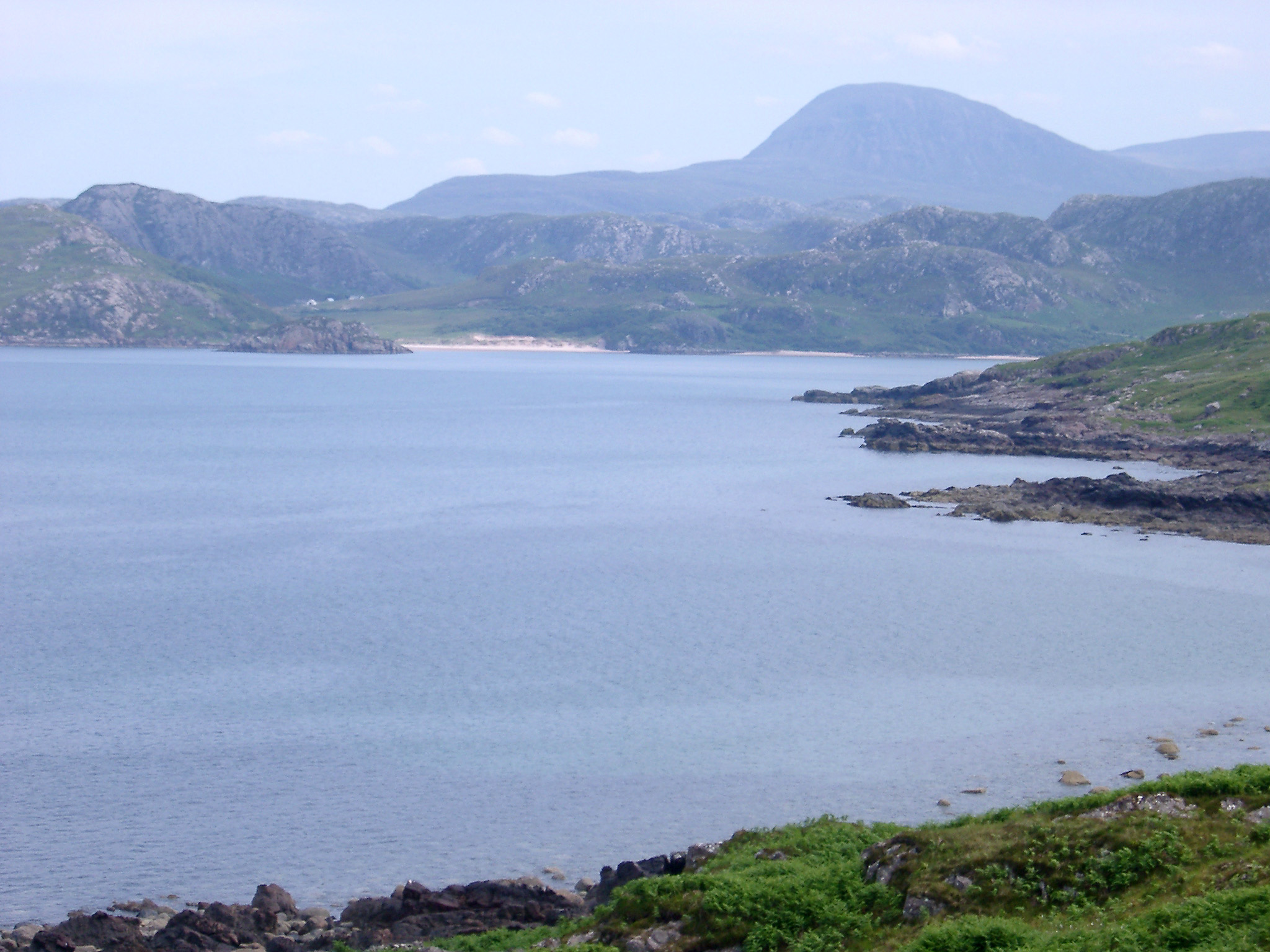 Scenic view of a loch in Scotland with inlets, bays and a golden beach backed by rugged mountains on a misty day