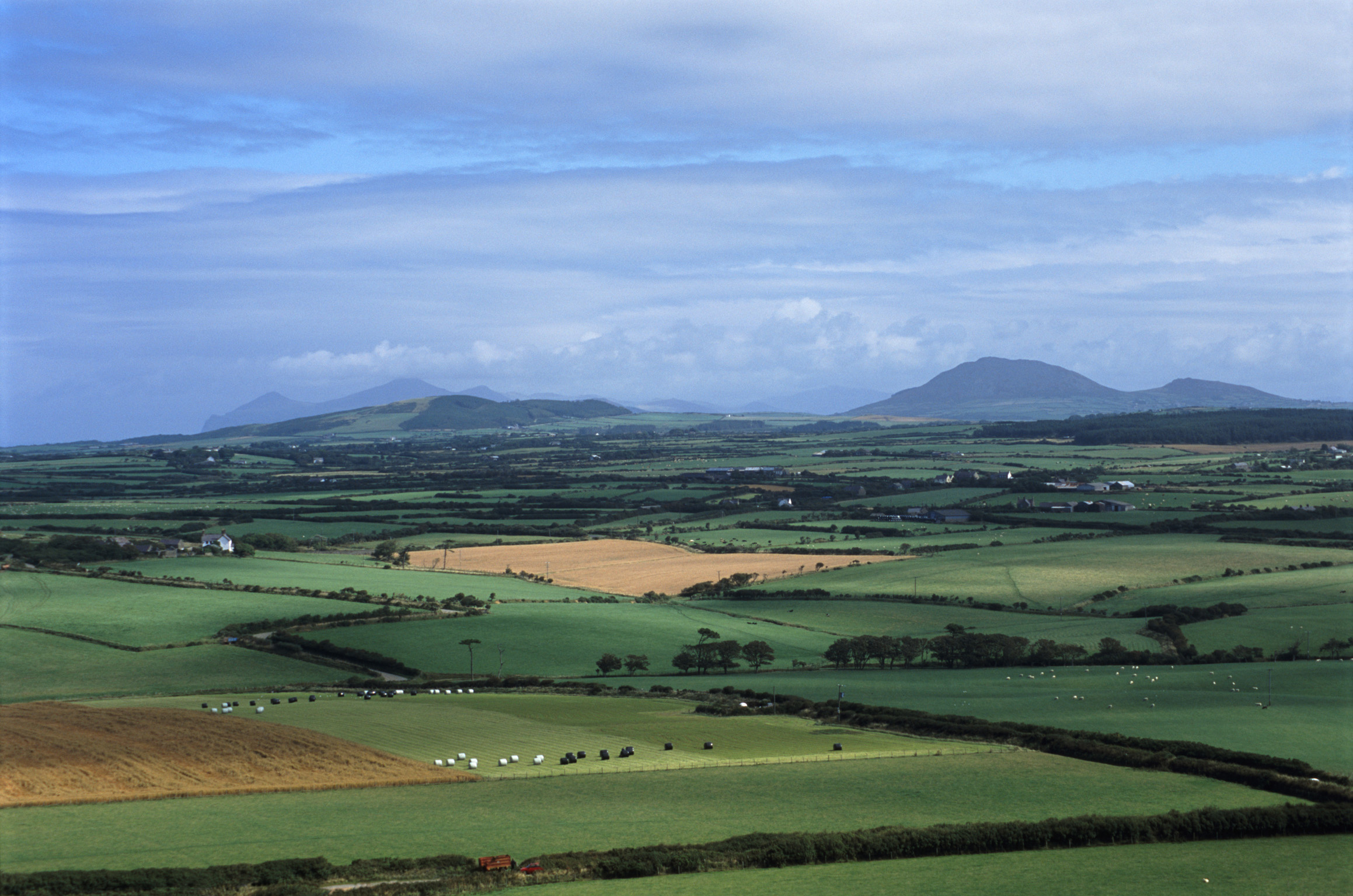 Patchwork of green agricultural fields on the Llyn peninsula with a scenic landscape view across to distant mountains