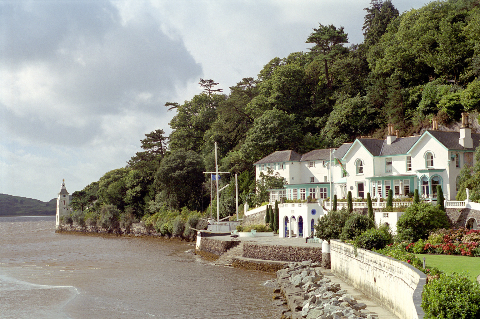 Scenic coastal landscape of the Portmeirion Hotel, Gwynedd, North Wales, overlooking the water amidst lush greenery