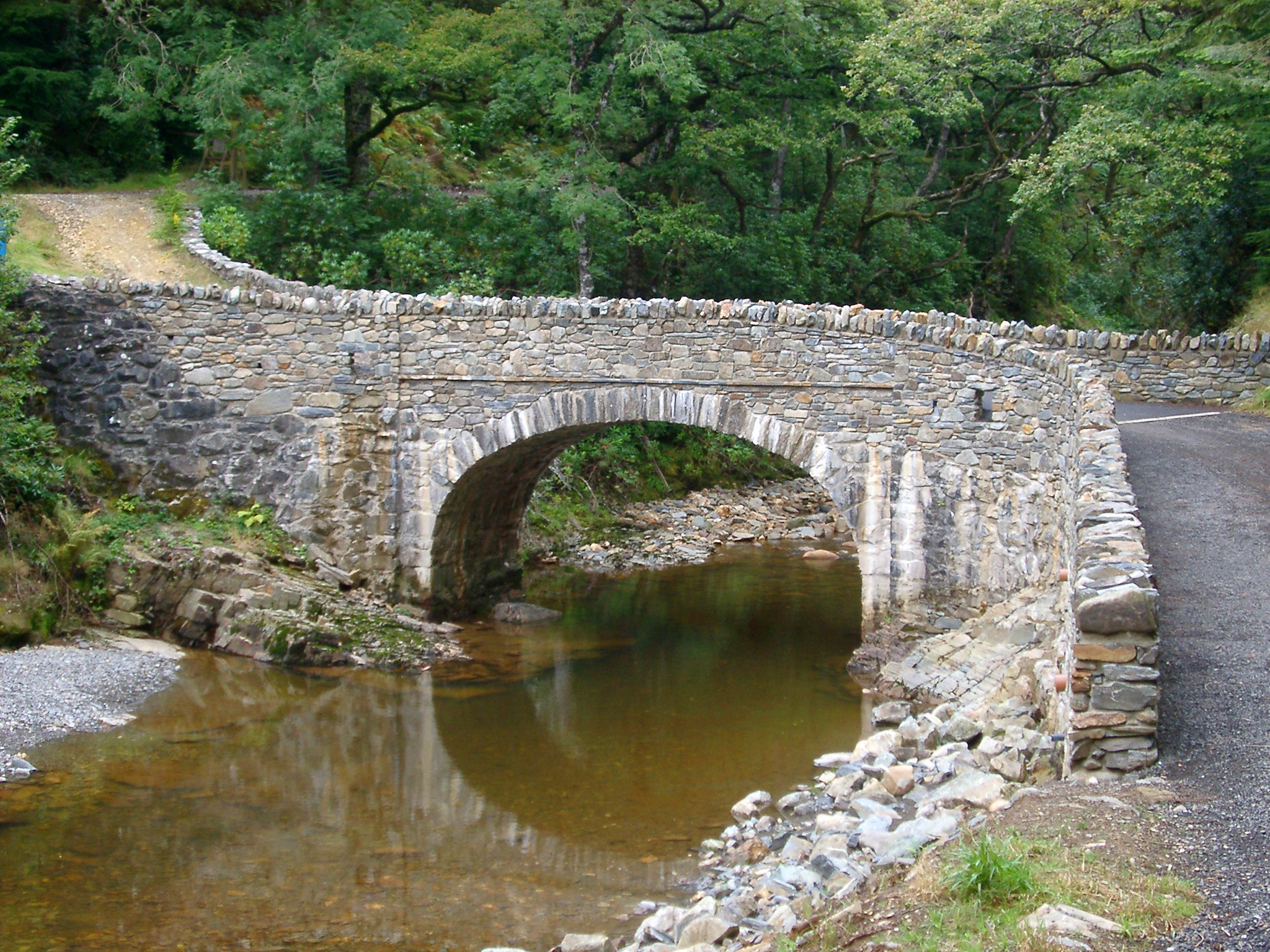 Narrow Stone Arch Bridge Crossing Over River Through Forest