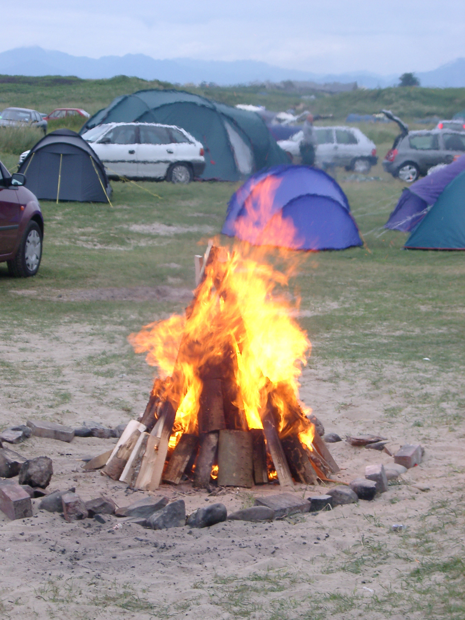 Campfire burning in a campsite amongst rows of small tents and parked cars