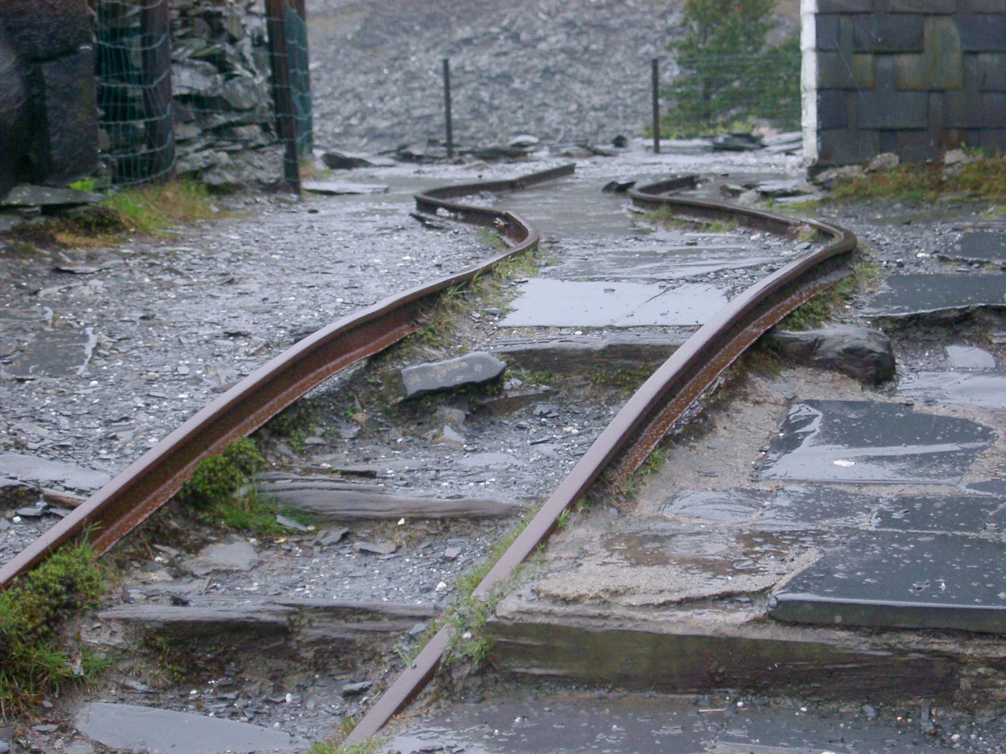 Damaged bent tracks in an old abandoned slate mine, low angle view showing the abrupt curve