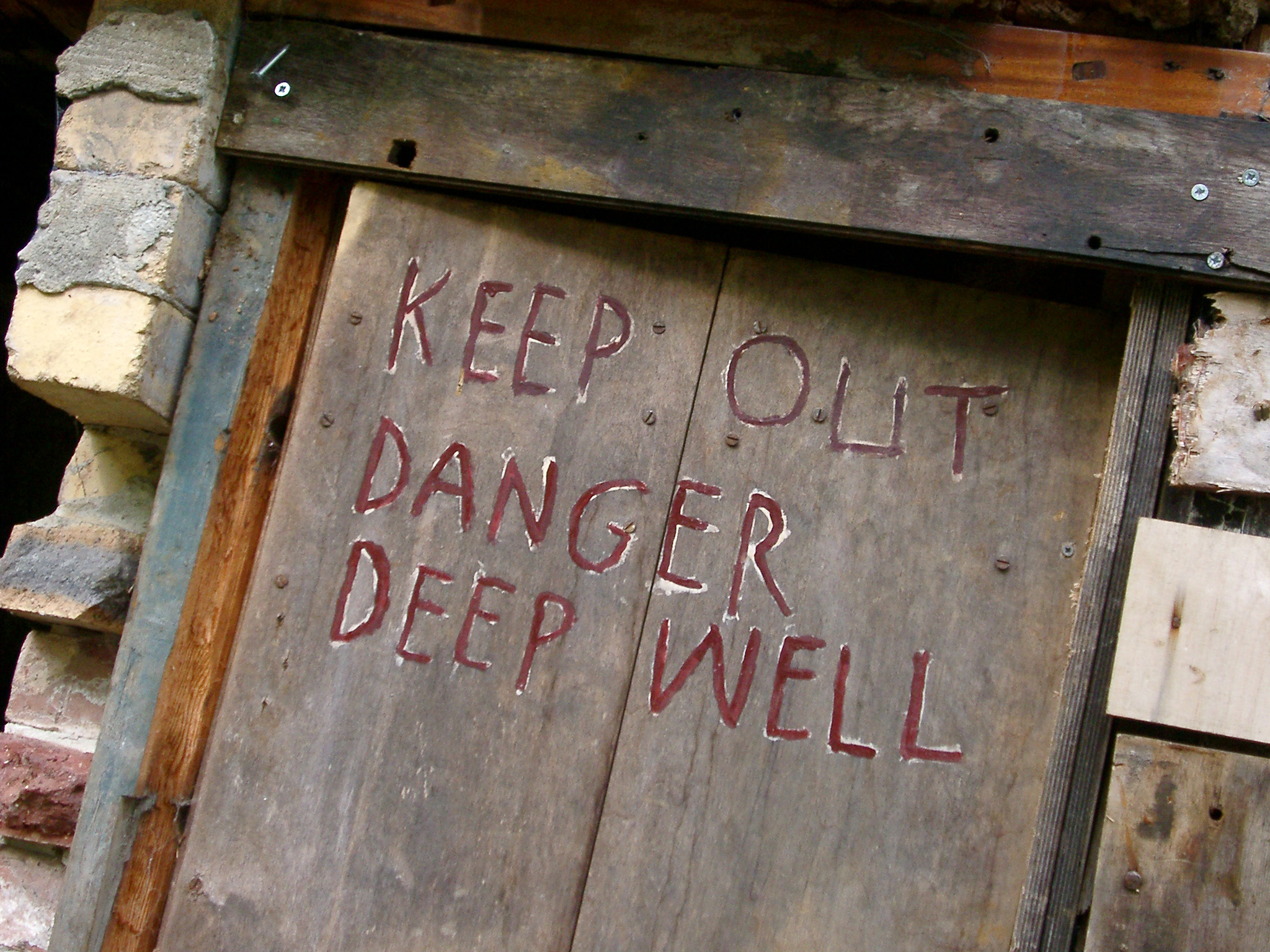 Closed up mine entrance with a wooden door and the warning - Keep out, danger deep well - painted on the exterior