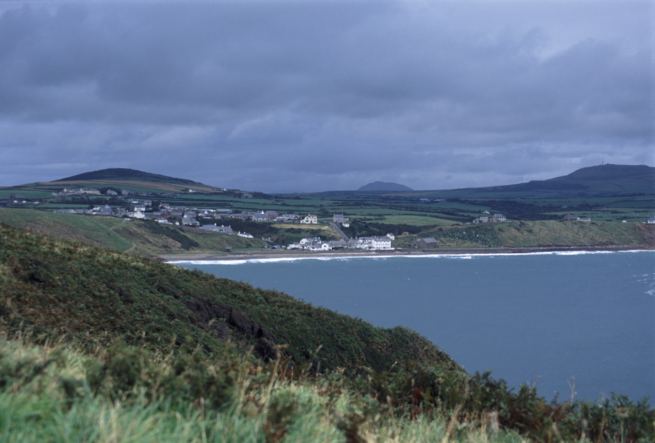 Picturesque village of Aberdaron on the Llyn peninsula in Wales with whitewashed buildings nestled around a sandy beach amidst rolling green hills