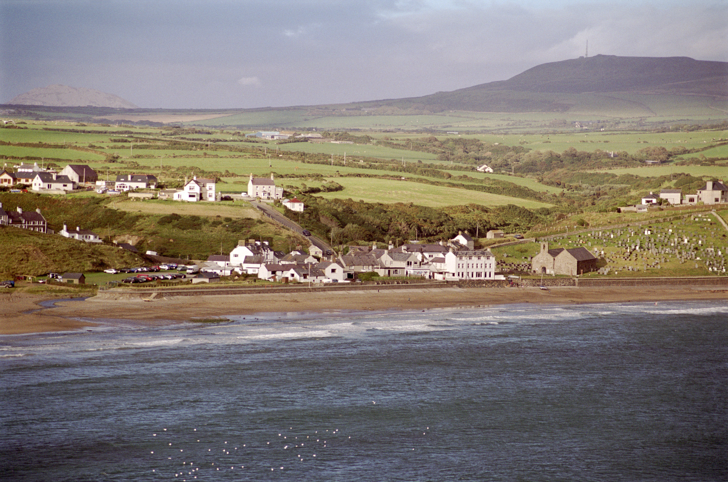 Extensive View of Aberdaron Village of Gwynedd, United Kingdom. Captured with Small Houses on Green Landscape Fronting the Sea.