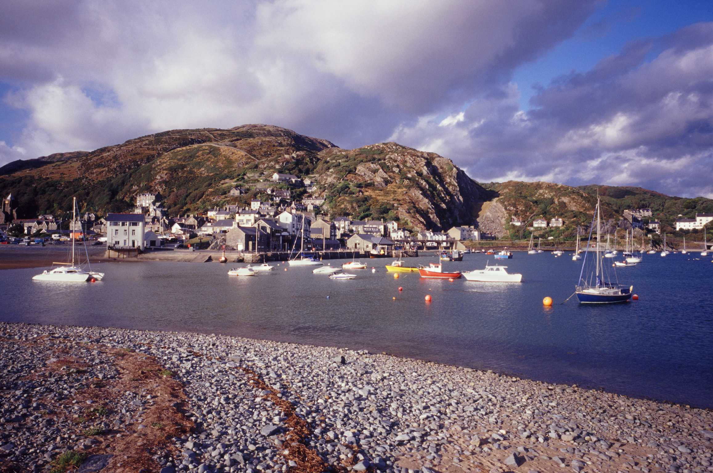 Scenic view of Barmouth, Gwynedd, Wales showing the waterfront with boats moored in the sheltered harbour of the bay