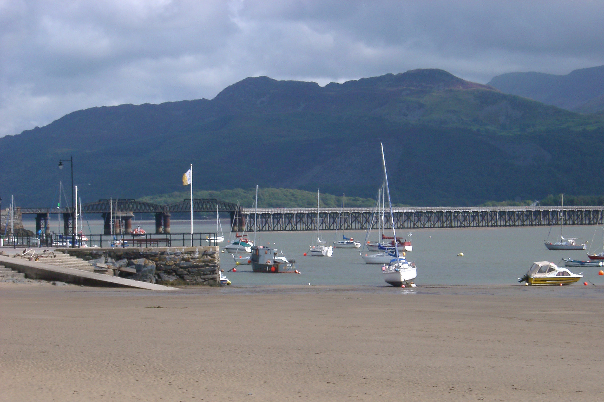 Barmouth rail viaduct with small fishing and pleasure boats moored in the sheltered harbour in the foreground